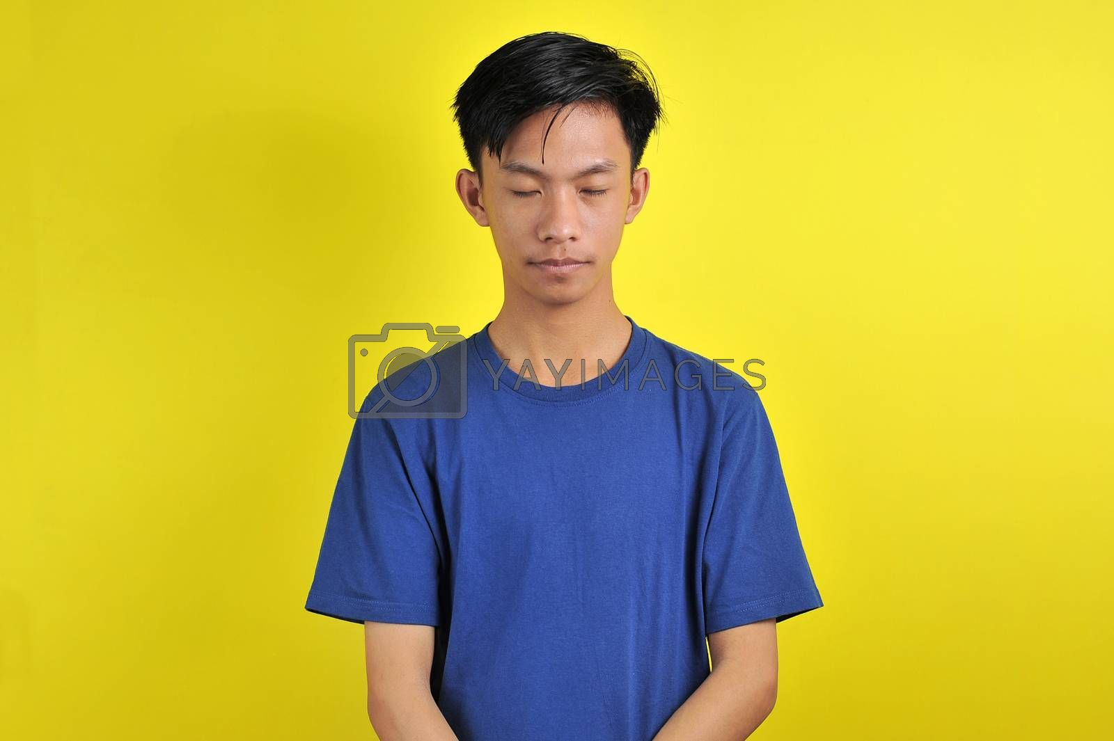 Portrait of young Asian man close his eyes, isolated on yellow background