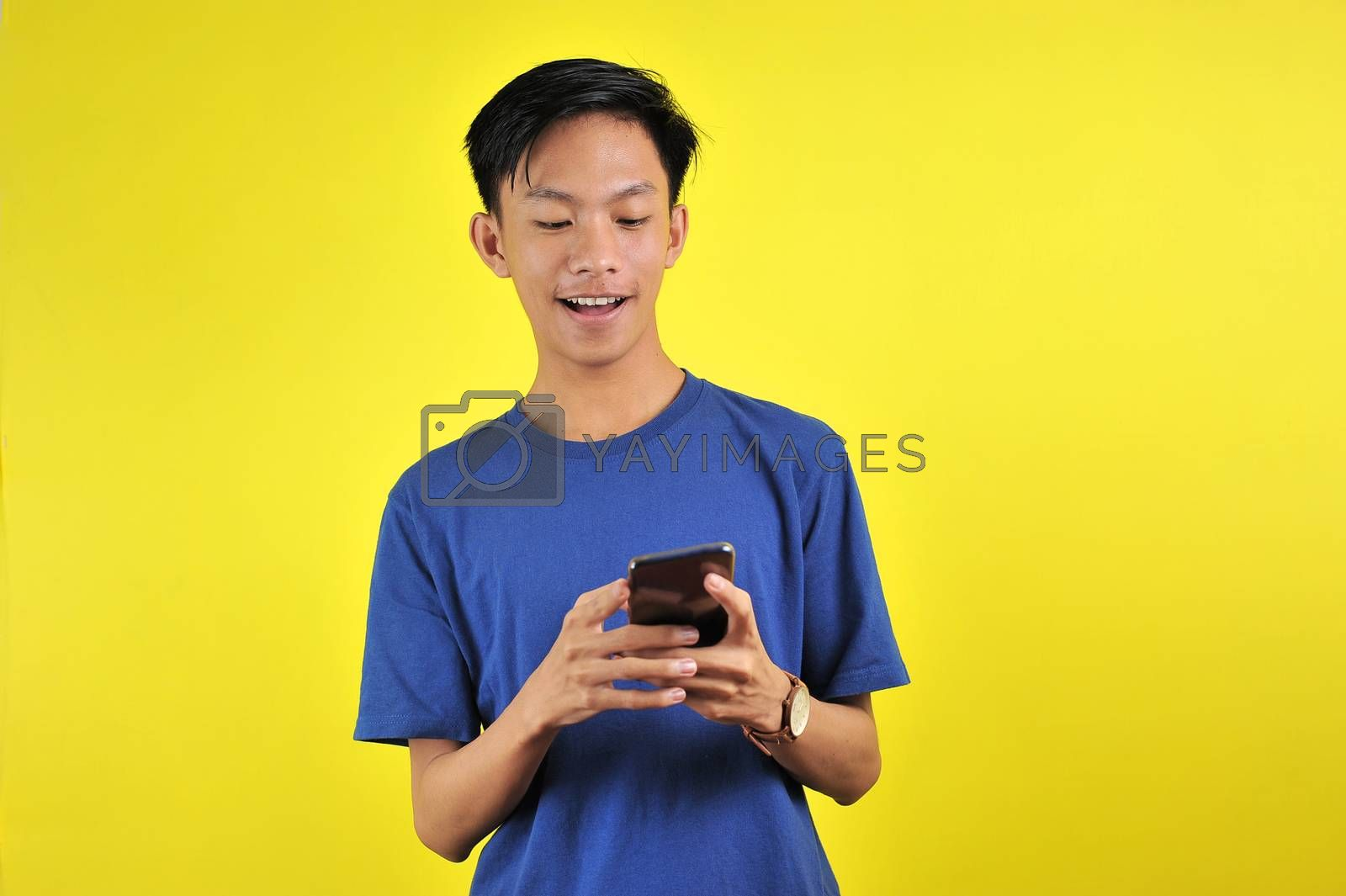 Happy of young good looking Asian man smiling using smartphone isolated on yellow background