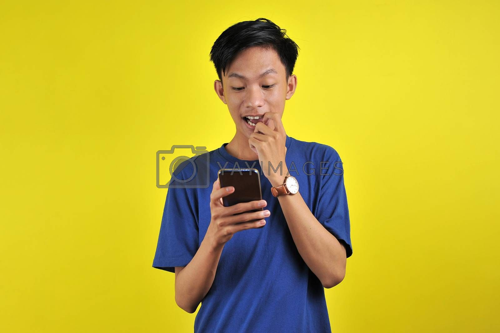 Shocked face of Asian man in white shirt looking at phone screen on yellow background.