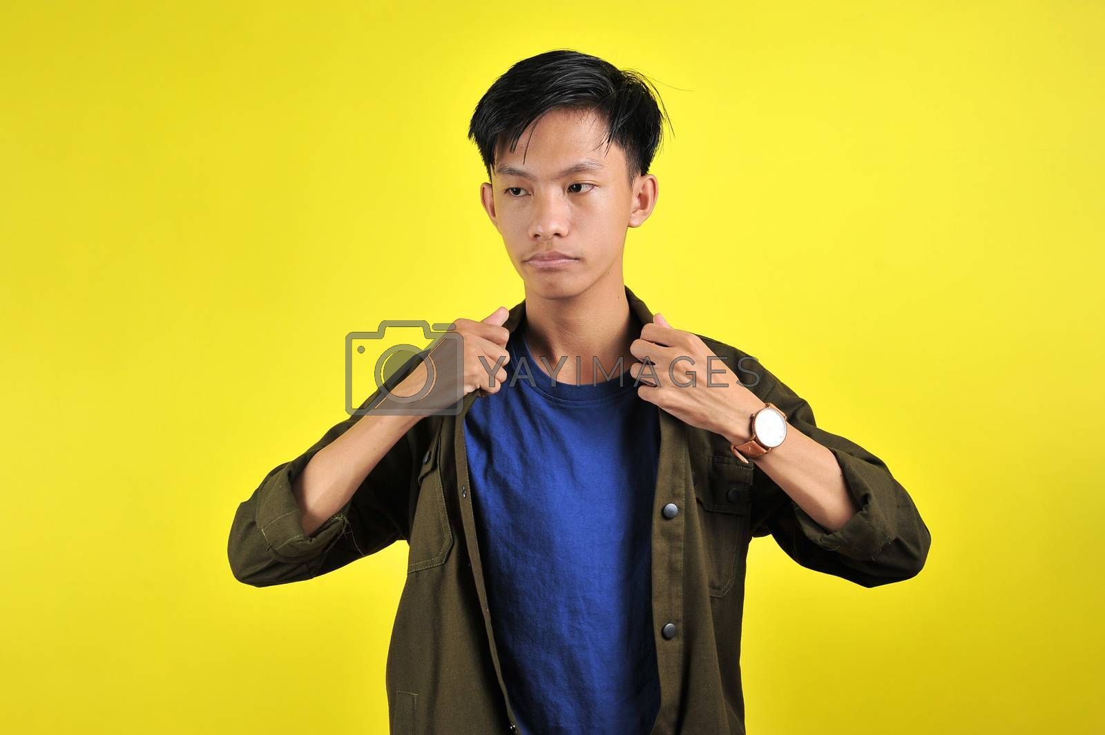 Portrait of young Asian man doing arrogant gesture, isolated on yellow background