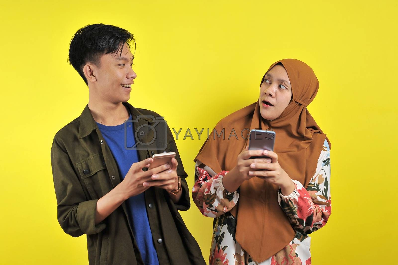 Photo of positive excited people man and woman screaming and looking at each other while both using mobile phones isolated over yellow background
