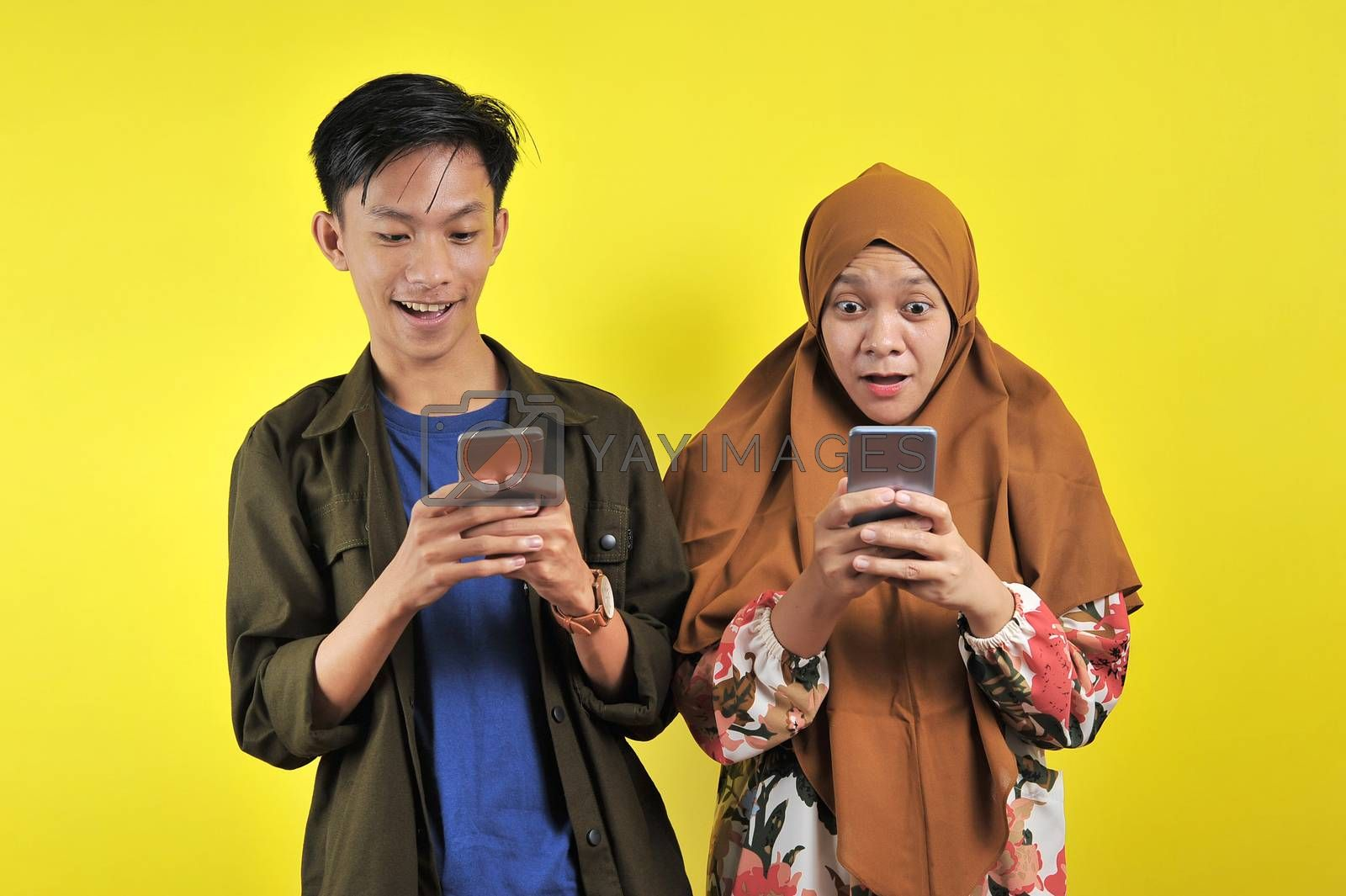 Woman and Young man, shock looking at smartphone display with positive emotion facial expression isolated yellow background