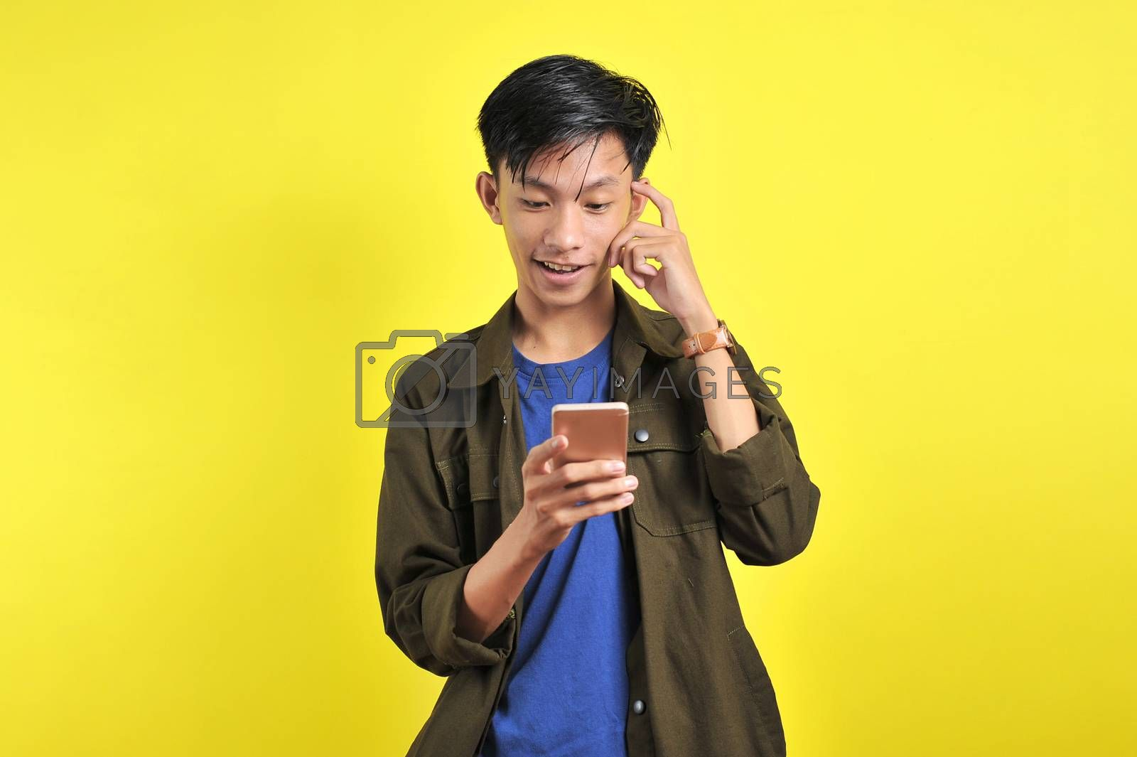 Portrait of smart person Young Asian man doing thinking gerture look at smartphone display, isolated on yellow