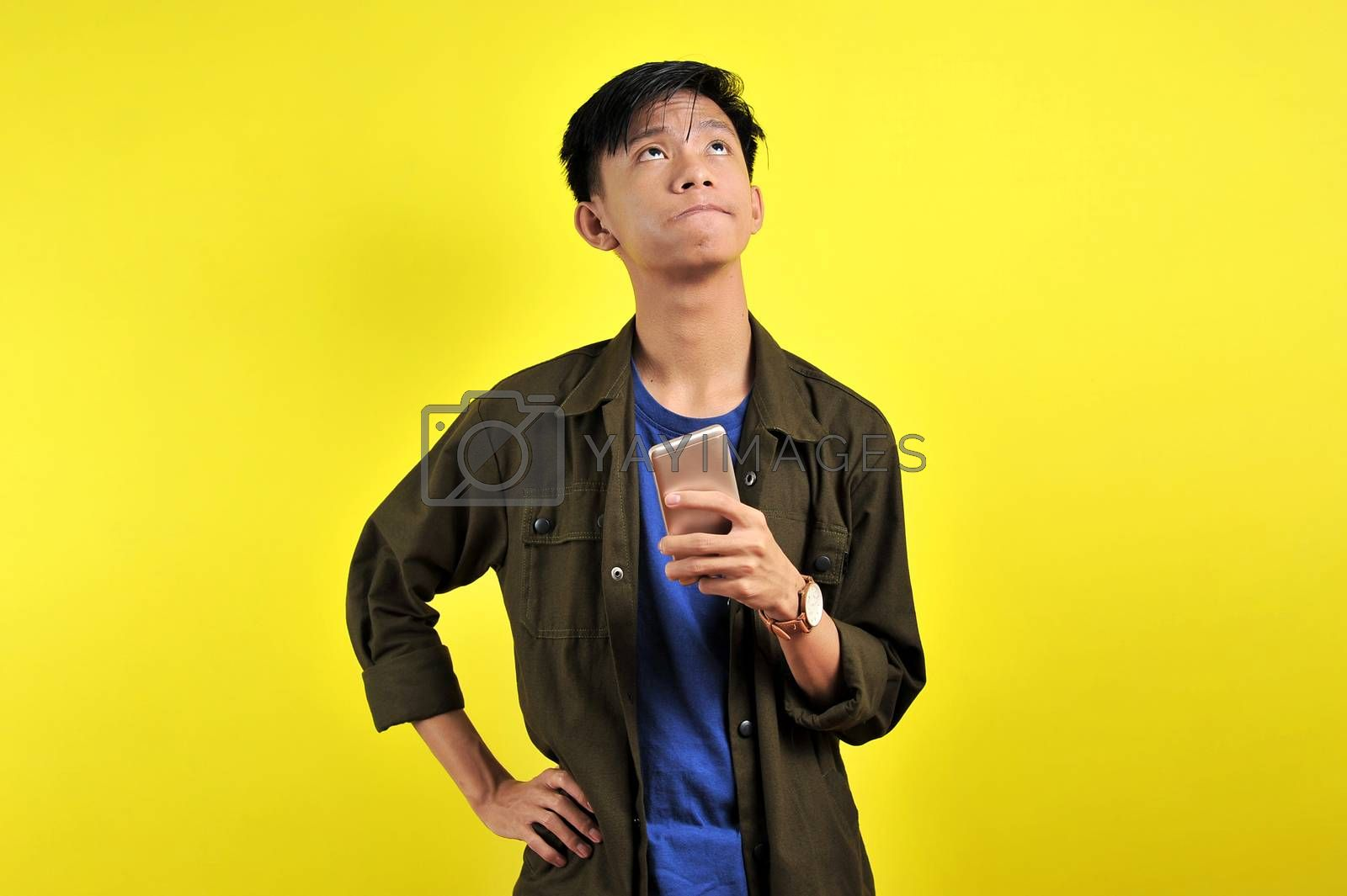 Happy young Asian man smiling using smartphone looking at blank by heruan1507