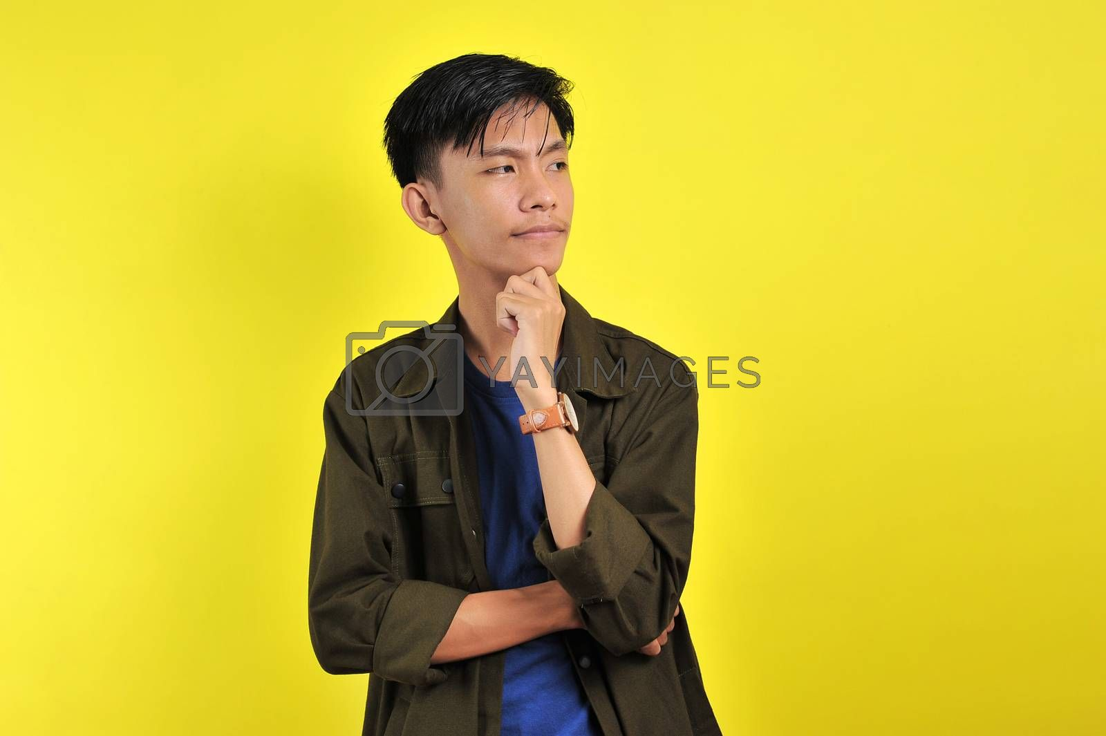 Handsome young Asian man looking at copy space or blank area, isolated on yellow background