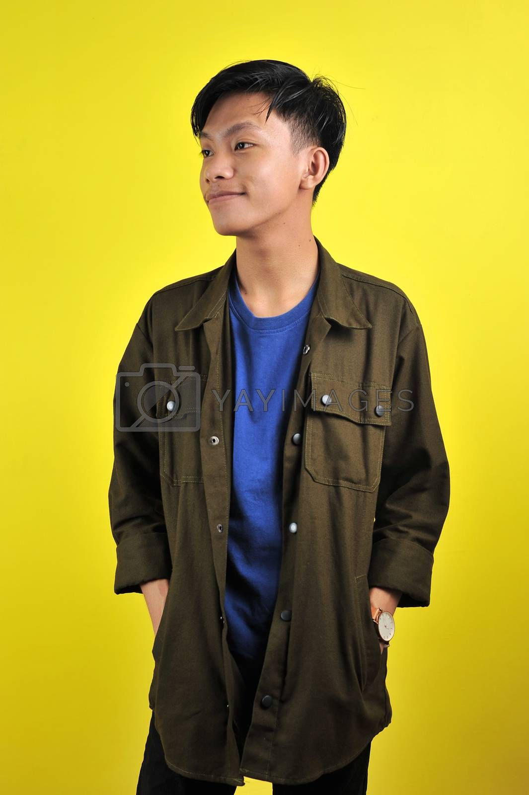 Confidence Asian young man wear casual t-shirts and jacket, isolated on yellow background