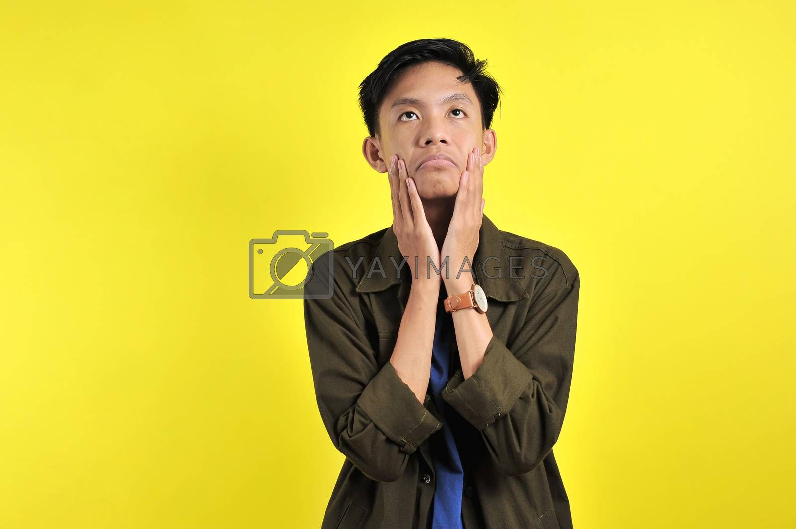 Confused man doing foolish gesture, disappointed expression, isolated on yellow background