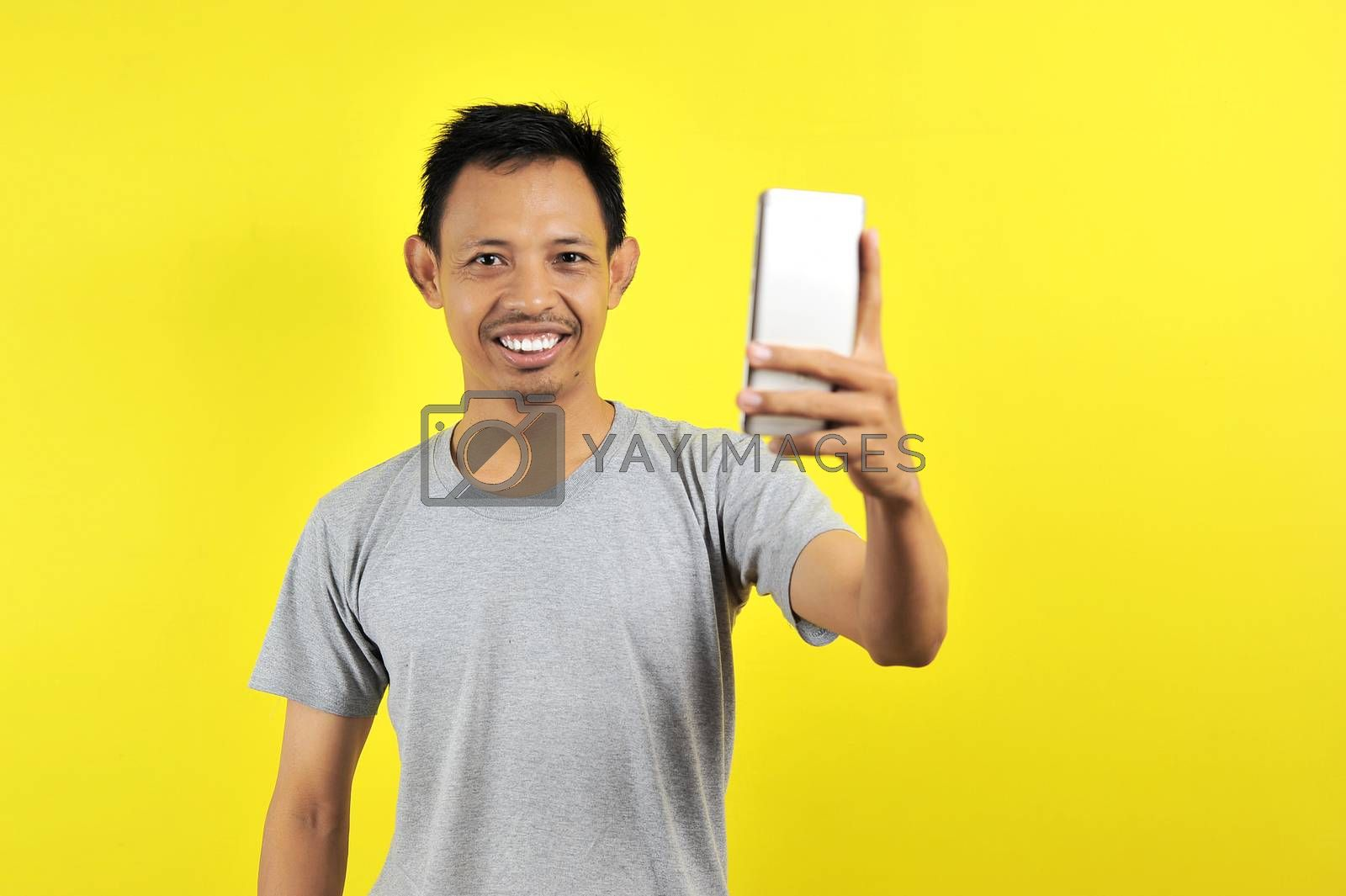 Portrait of cool cheerful Asian man having video-call with lover holding smart phone in hand shooting selfie on front camera, isolated on yellow background