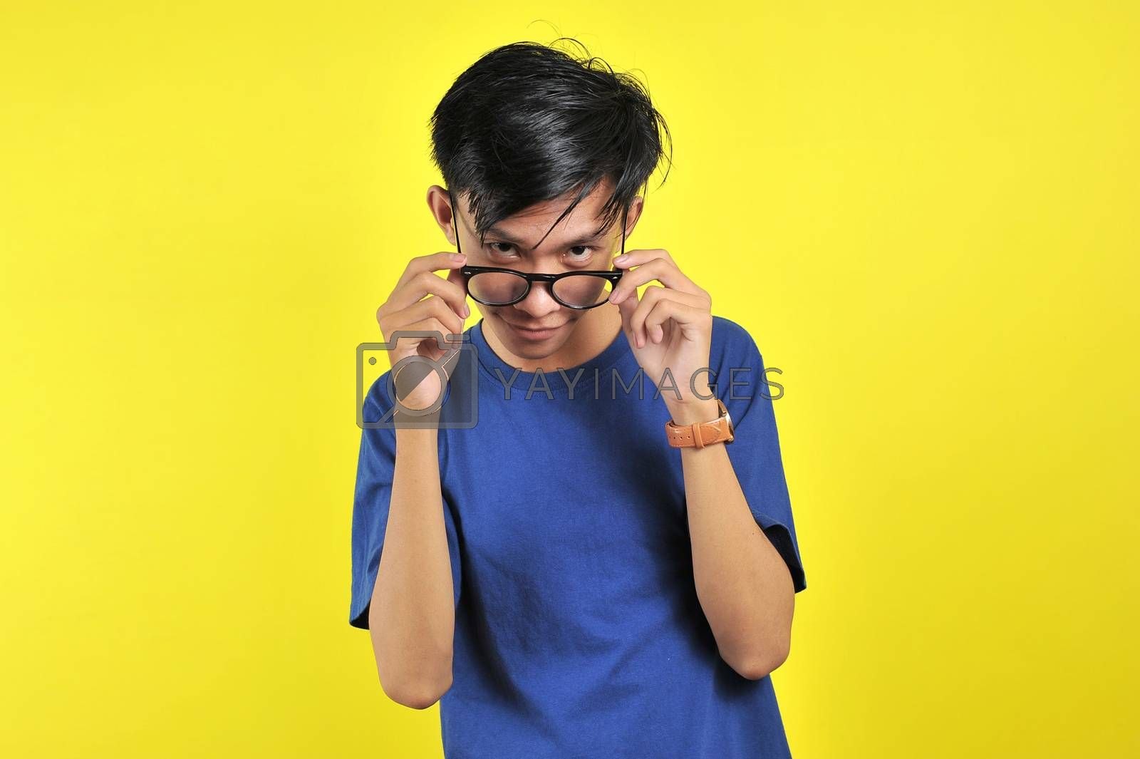 Close up portrait of attractive stylish charming confident, holding eyelets with hands, isolated on yellow background