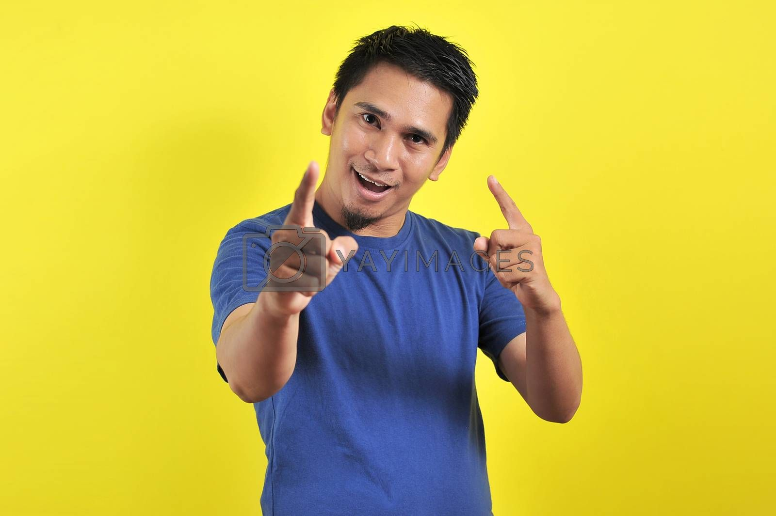 Young asian man happy and excited expressing winning gesture. Successful and celebrating on yellow background