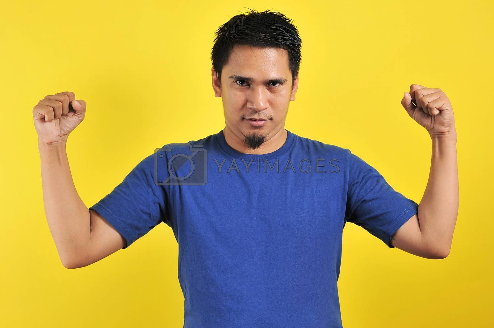 Handsome young Asian man showing muscle, strong gesture and showing power, isolated on orange background