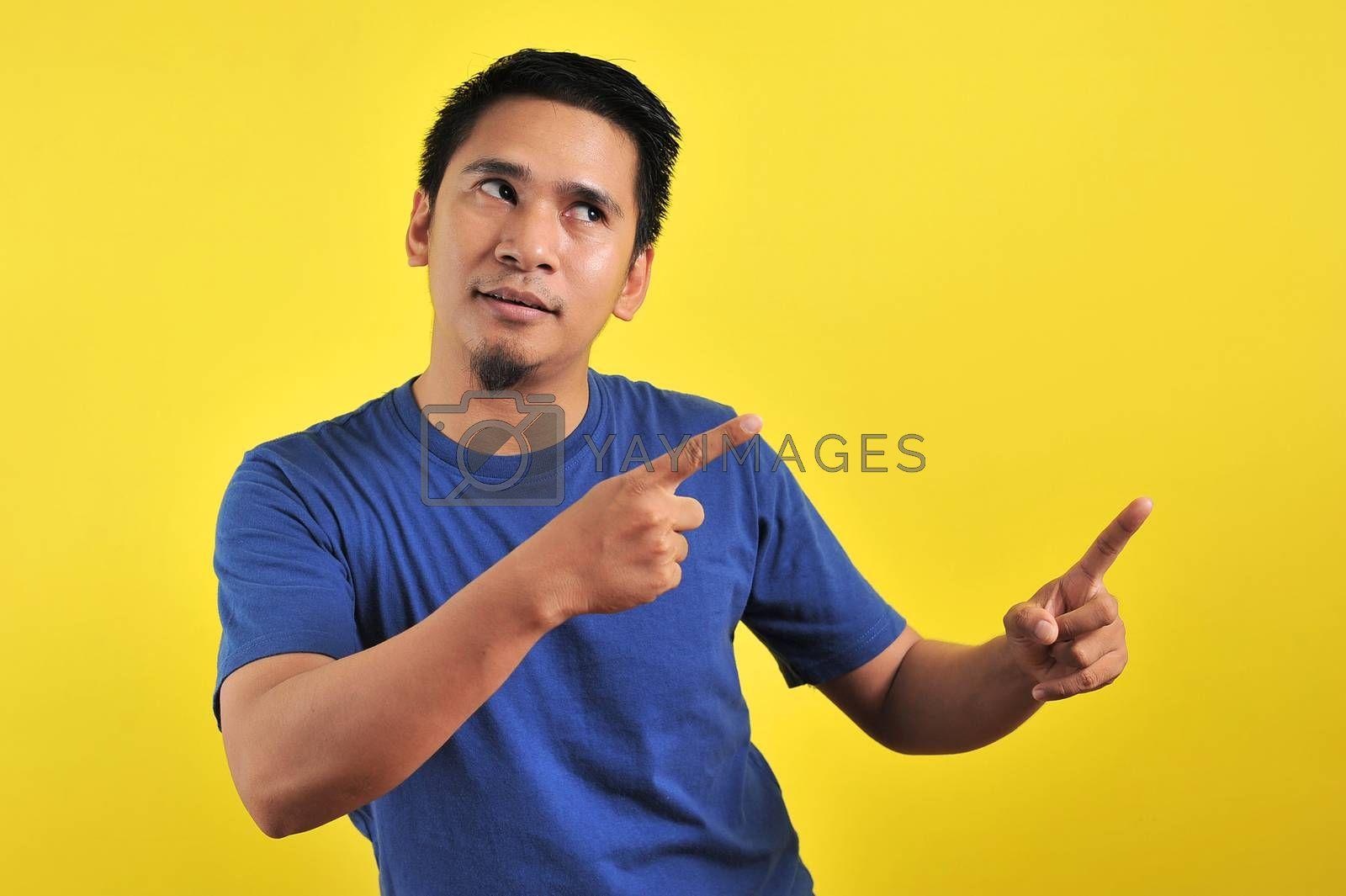 Friendly-looking lively pleasant Asian male with white t-shirt smiling delighted look at copy space joyful. Self-assured pointing, on yellow background