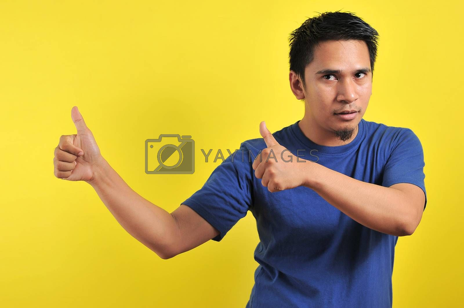 Happy young Asian man giving two thumbs up, isolated on light orange background