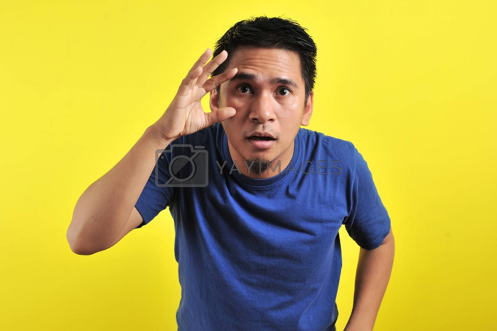 Portrait of Young Asian man open his eyes, isolated on yellow background