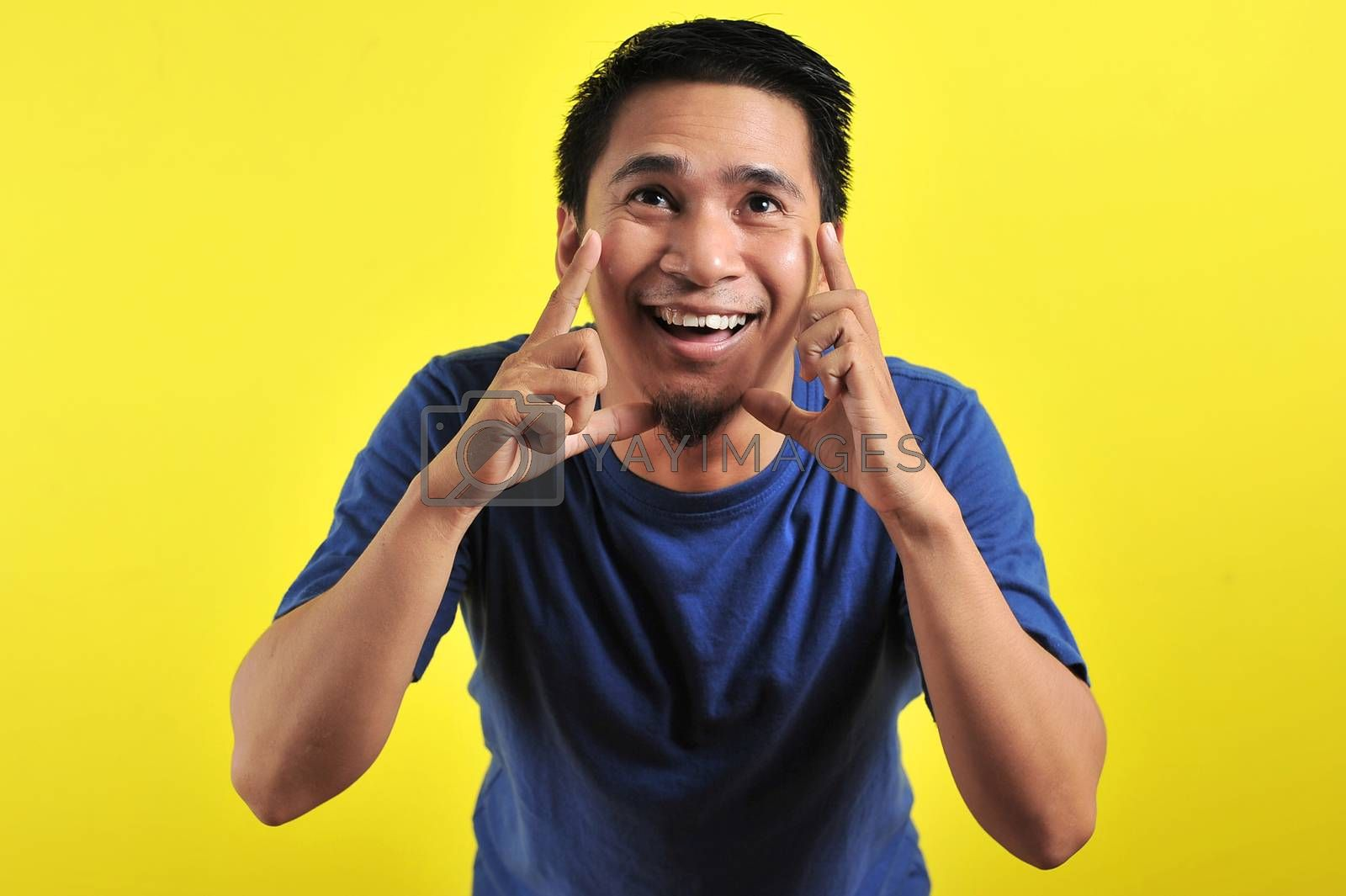 Close up portrait of young man yelling with open mouth, isolated on yellow background