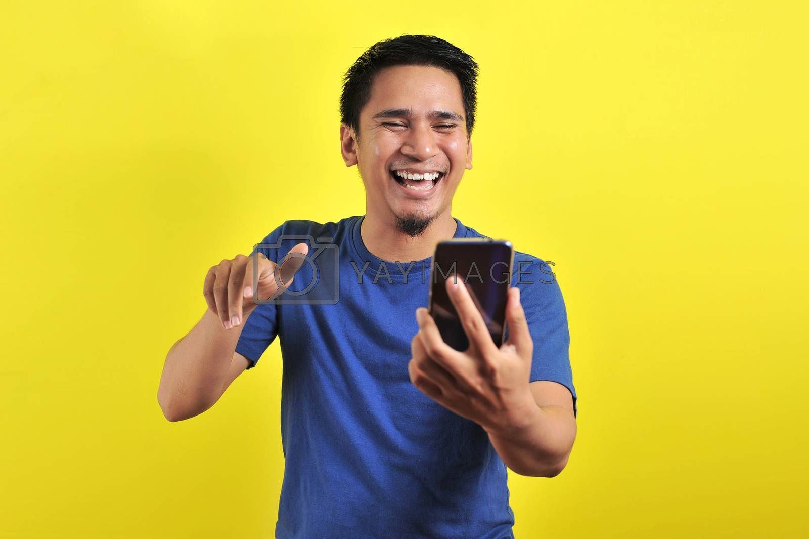 Happy of young good looking Asian man smiling using smartphone by heruan1507