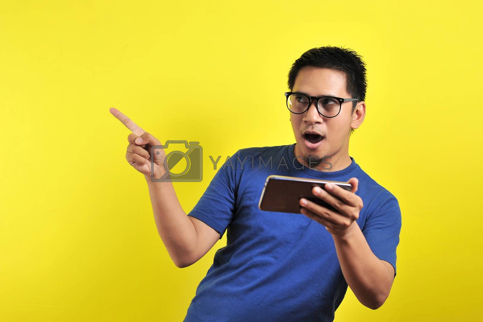 Happy young Asian man shocking using smartphone looking at blank area, isolated on yellow background