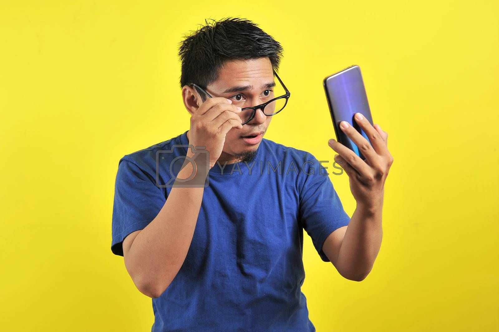 Asian man shocked what he see in the smartphone, isolated on yellow background