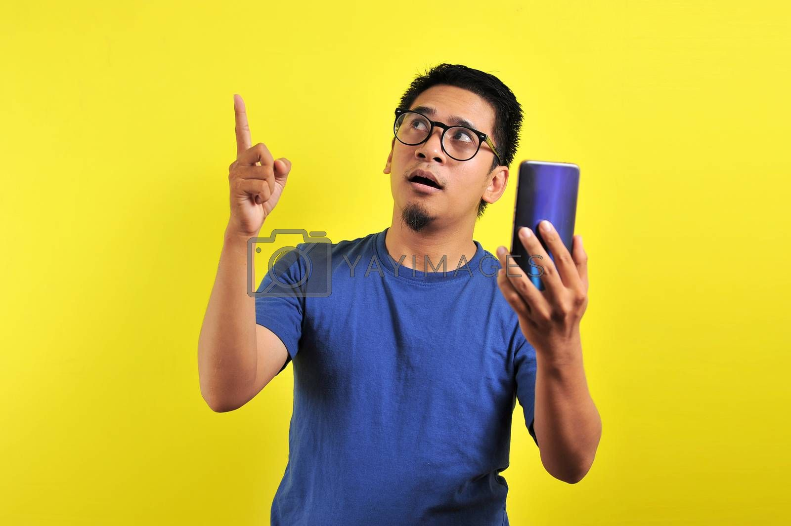 Happy young Asian man smiling using smartphone looking at blank area, isolated on yellow background