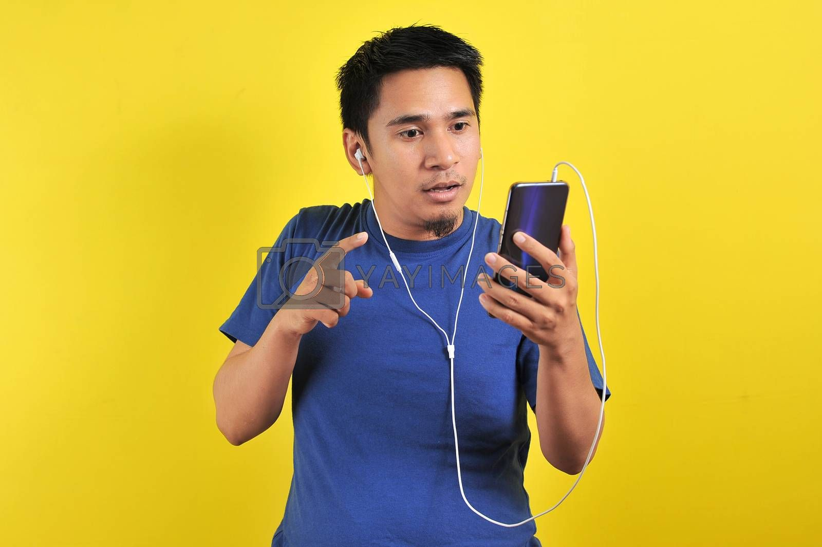 Asian man in casual blue t-shirt wearing headset listening to music from smartphone, shock expression, on yellow background