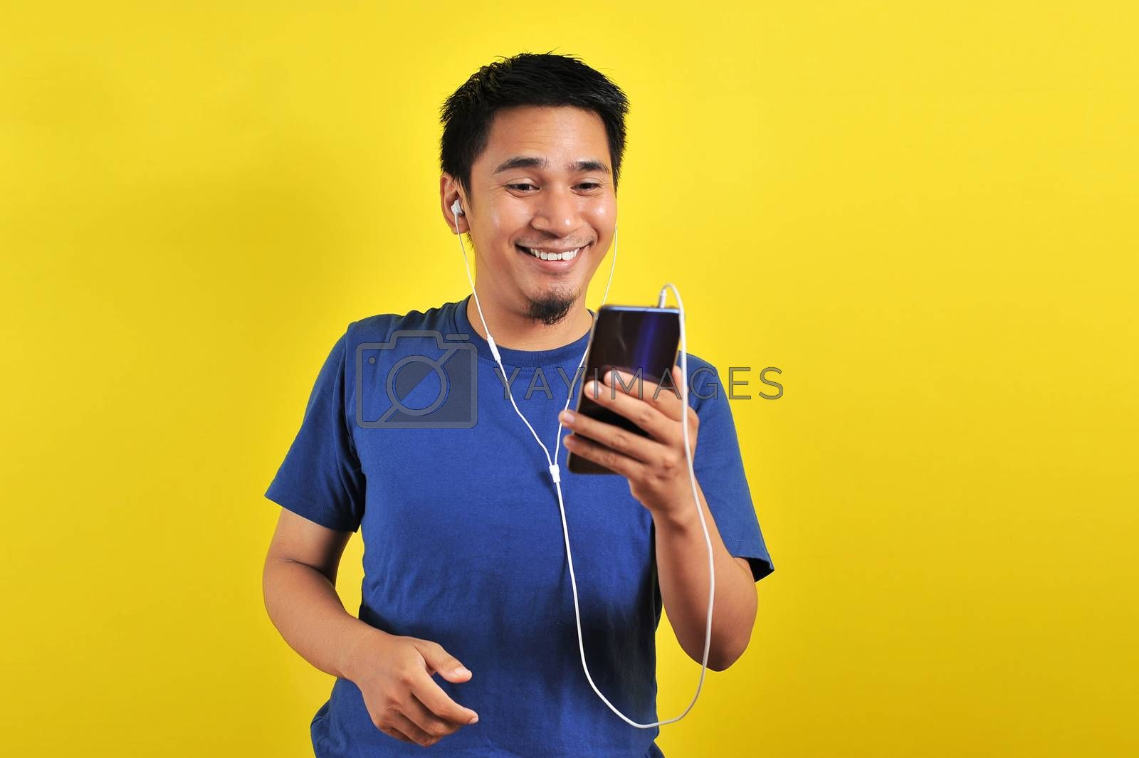 Asian man in casual blue t-shirt happy wearing headset listening to music from smartphone, isolated on yellow background.