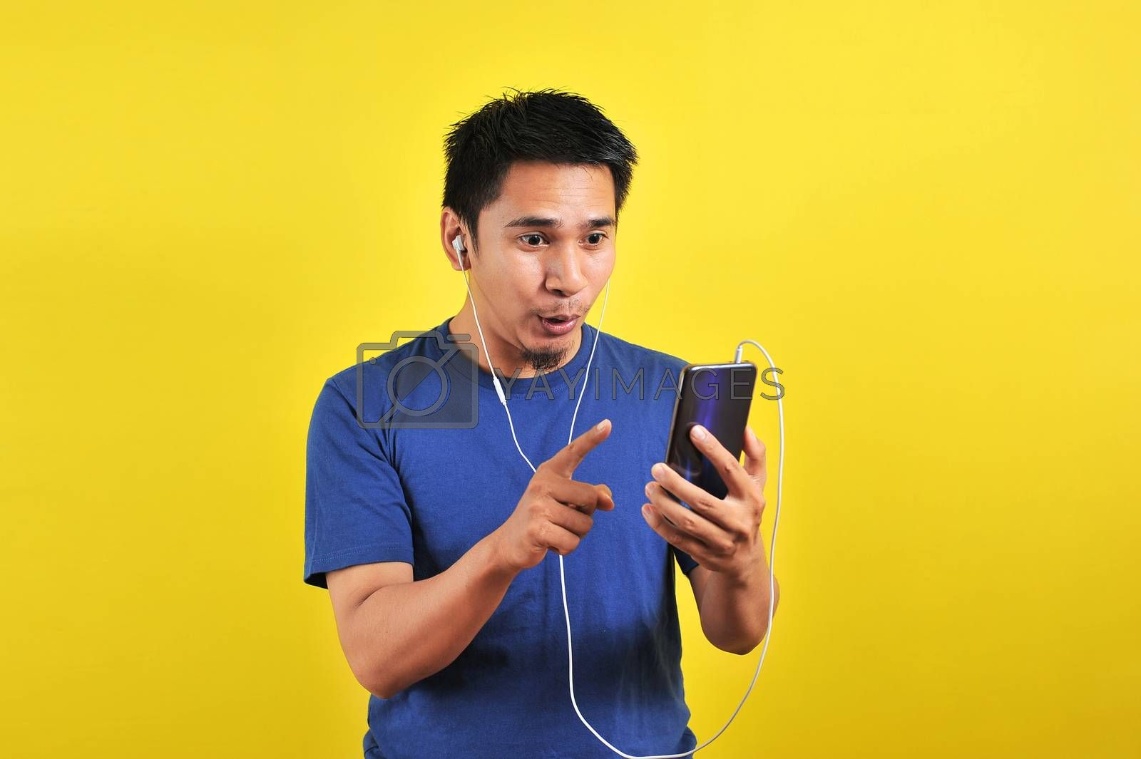 Portrait of excited Asian man surprised to find a trending song on online, isolated on yellow background