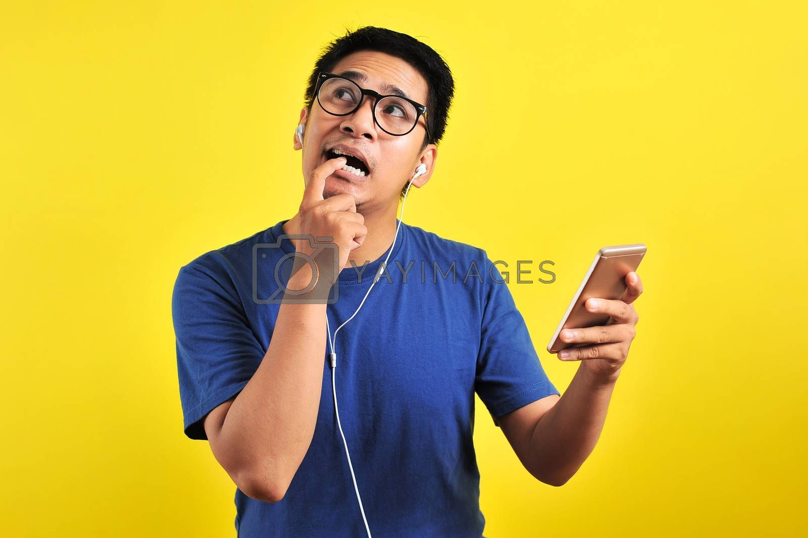Portrait of confused Young Asian man bitting his finger and listening live music from smartphone with headset, isolated on yellow background