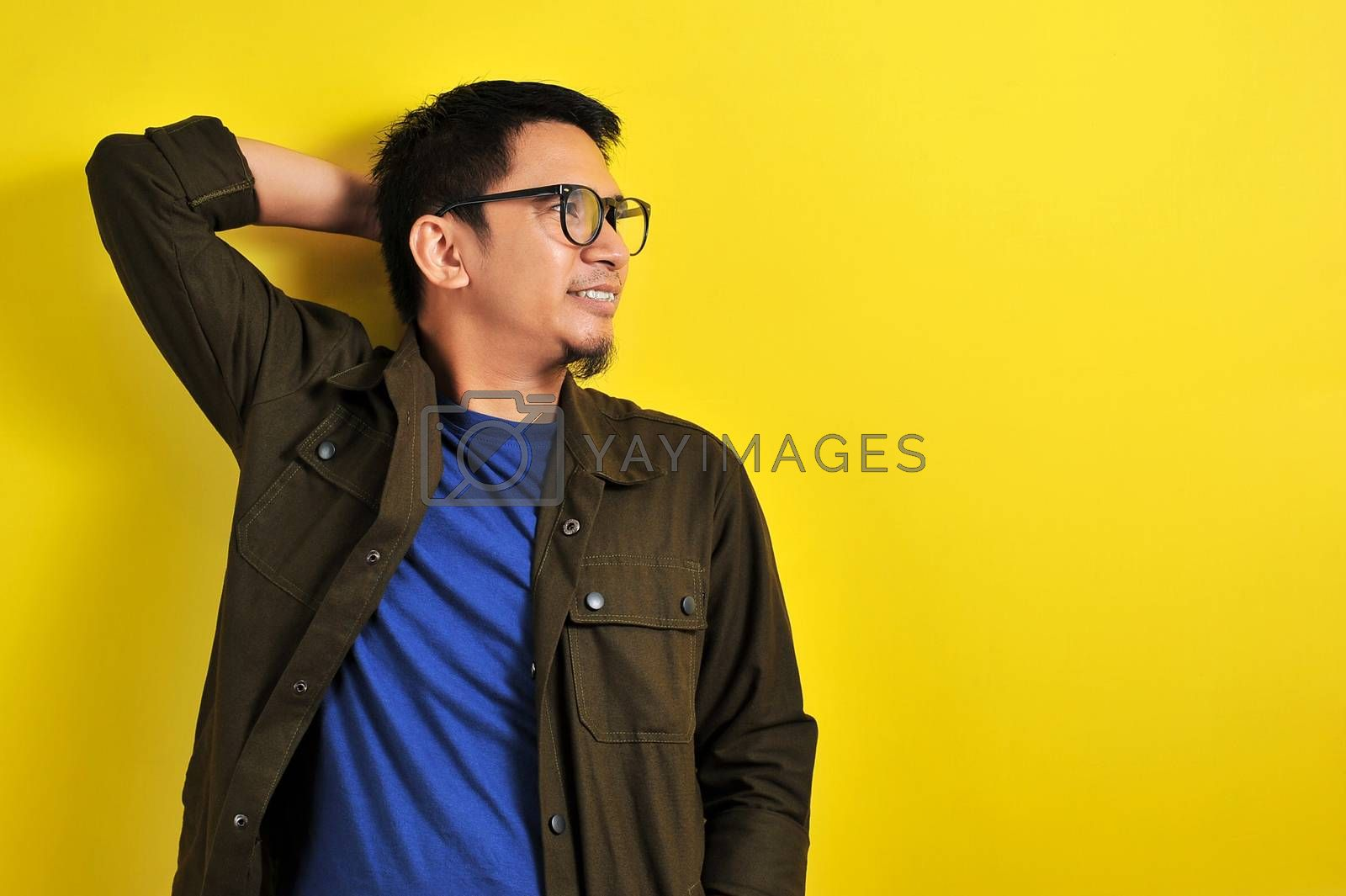 Asian man wearing glasses smiling look at copy, isolated on yellow background
