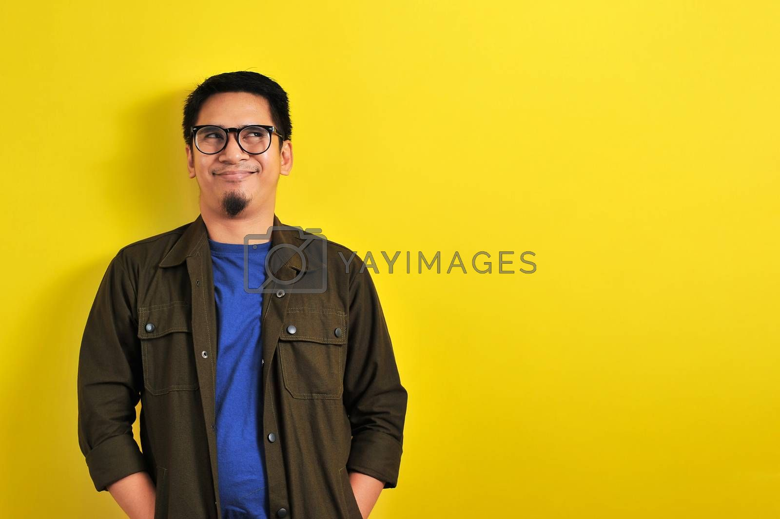 Asian Man with humorist face or funny face look at copy space, isolated on yellow background