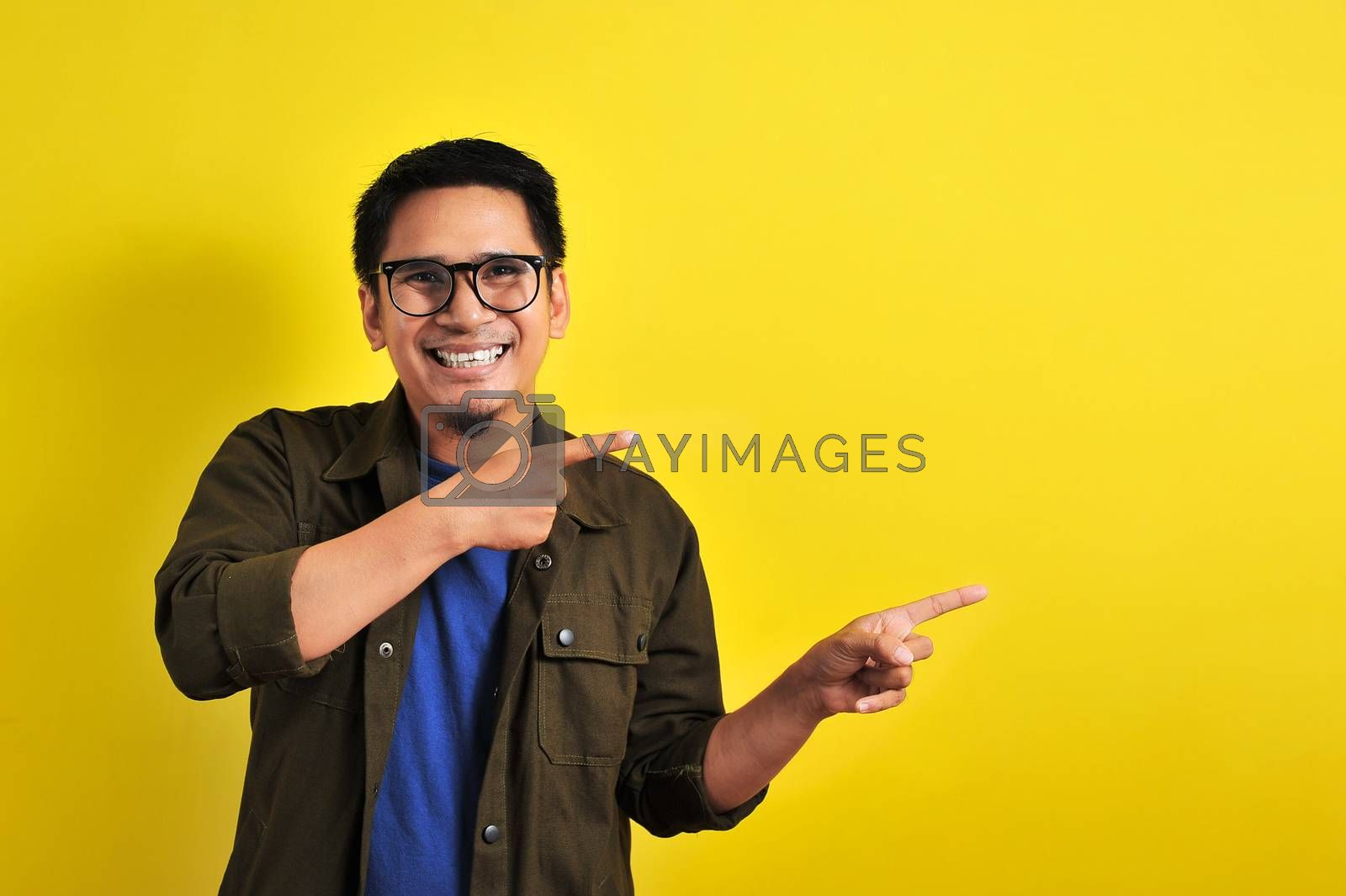 Friendly-looking lively pleasant Asian male with casual t-shirt smiling delighted look at copy space joyful. Self-assured pointing, on yellow background