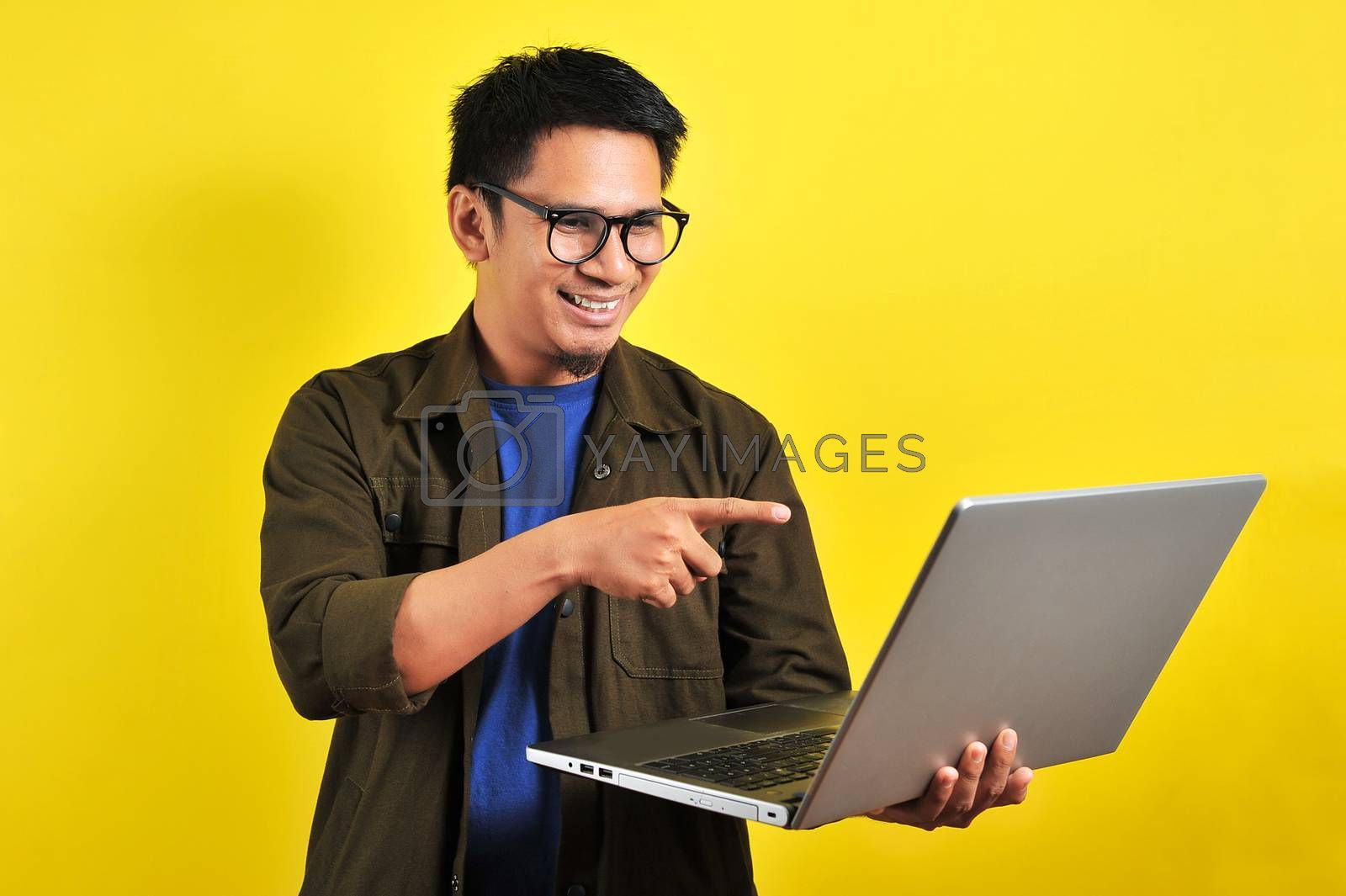 Smiling pleased handsome asian young male entrepreneur, pointing laptop display, isolated on yellow