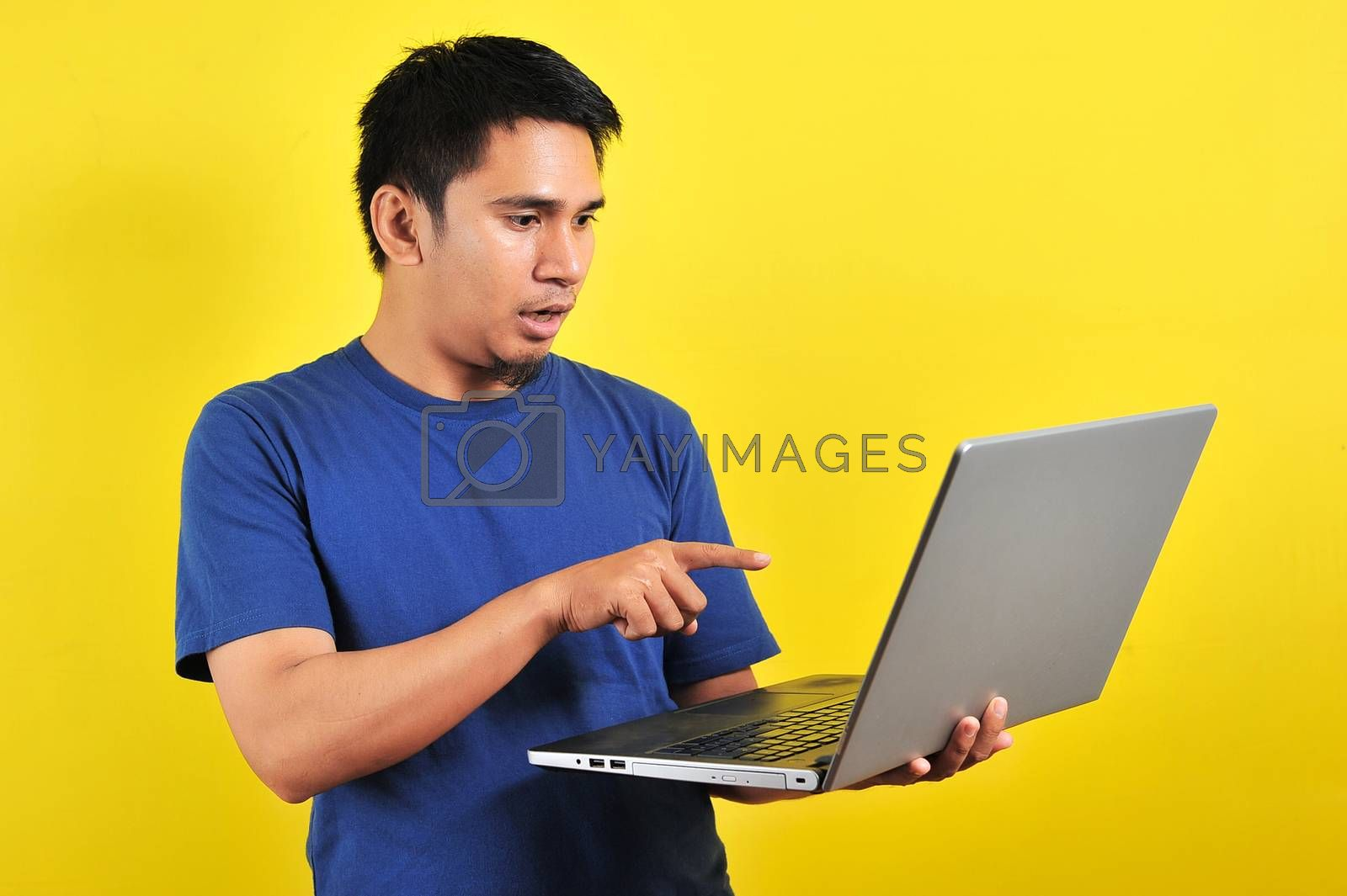 Asian man shocked what he see in the laptop, isolated on yellow background