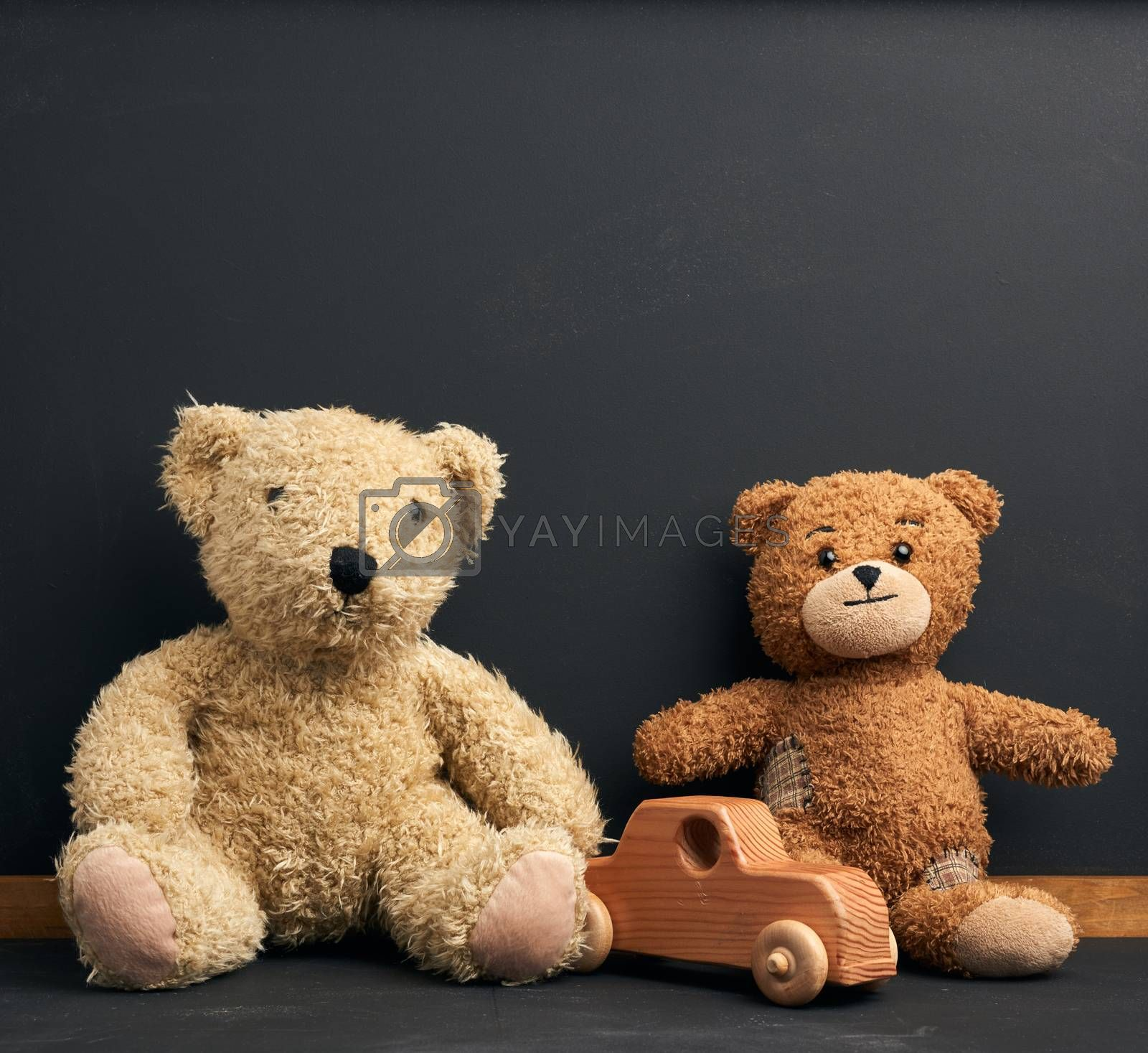 brown teddy bear sits on a brown wooden table, behind an empty black chalk board, place for an inscription, back to school