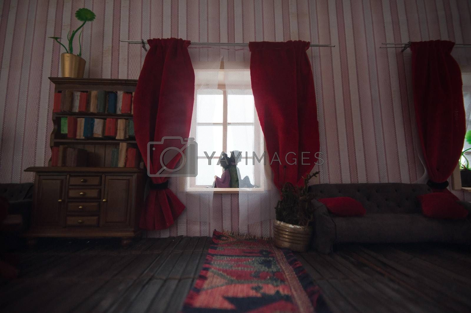 A realistic dollhouse living room with furniture and window. Romantic couple sitting on window. Artwork table decoration with handmade realistic dollhouse. Selective focus.
