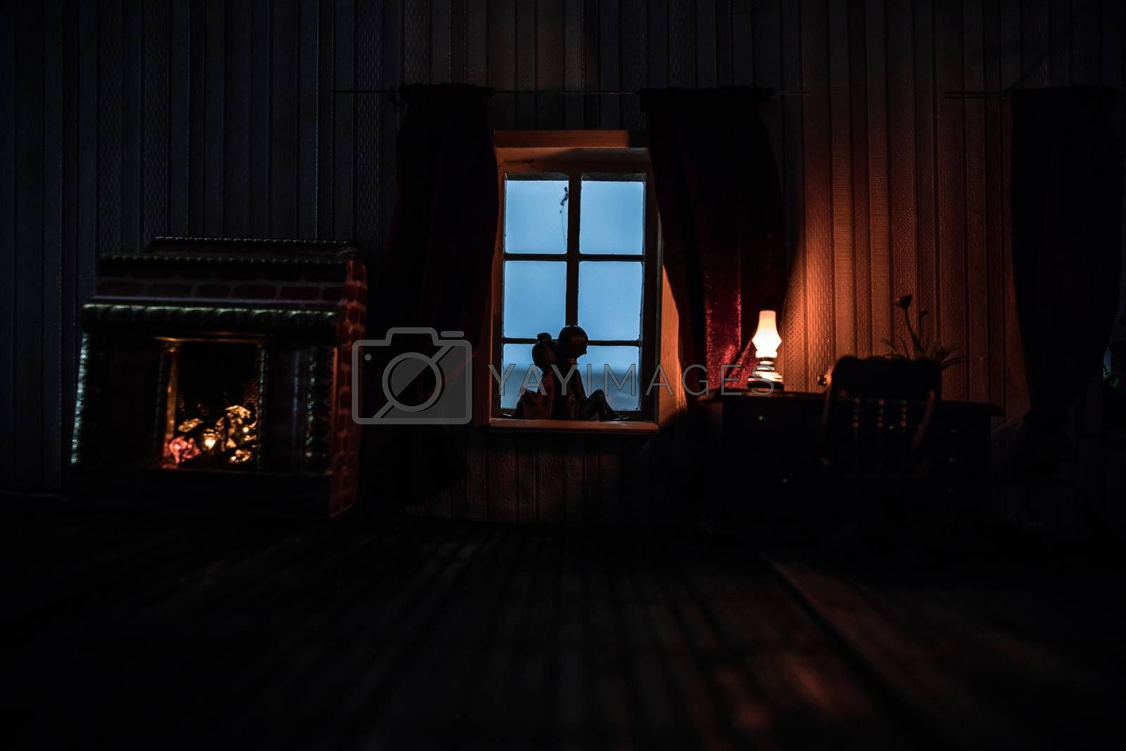 A realistic dollhouse living room with furniture and window at night. Romantic couple sitting on window. Artwork table decoration with handmade realistic dollhouse. Selective focus.