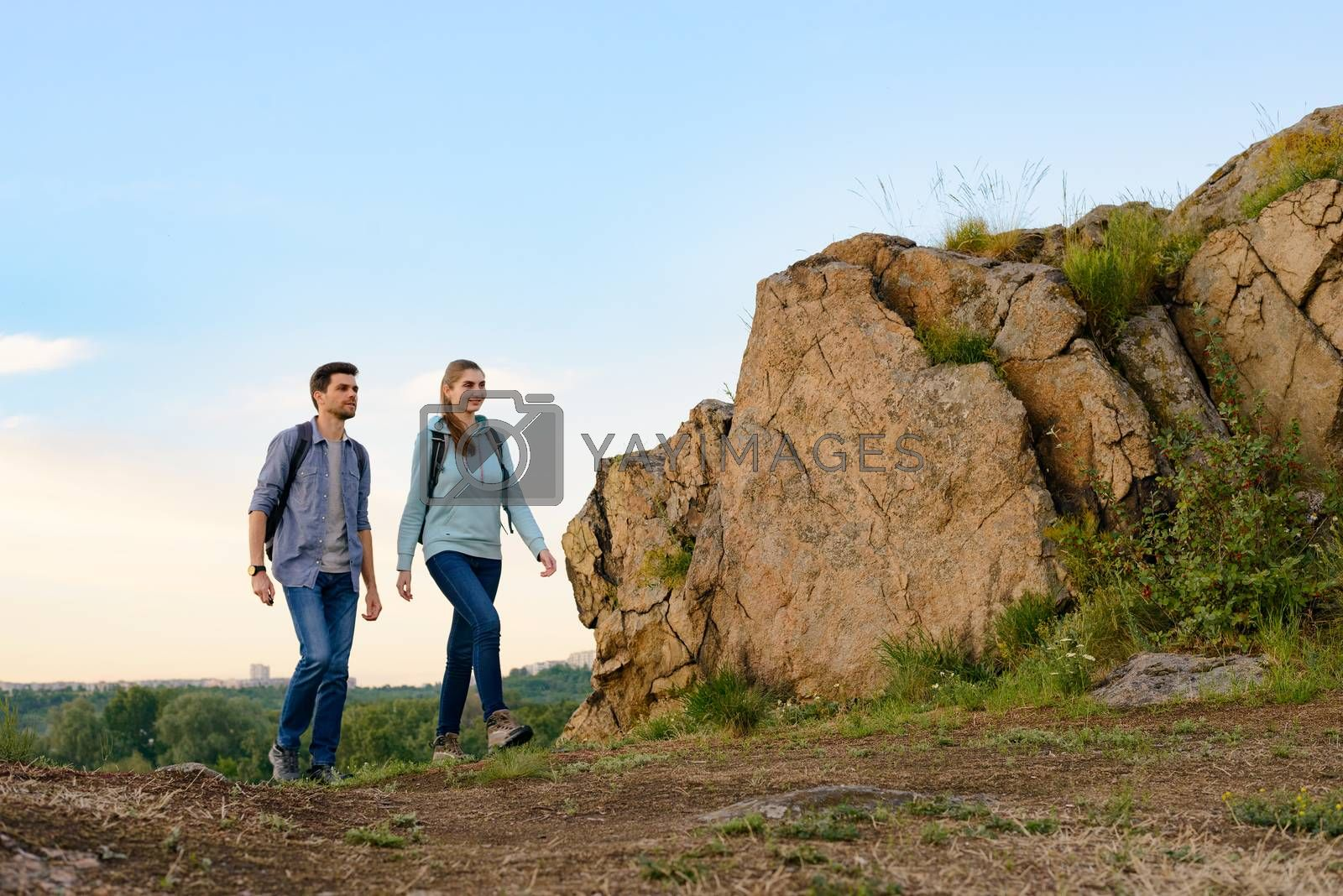 Couple of Happy Travelers Hiking with Backpacks on the Beautiful Rocky Trail at Summer Sunset. Family Travel and Adventure Concept.