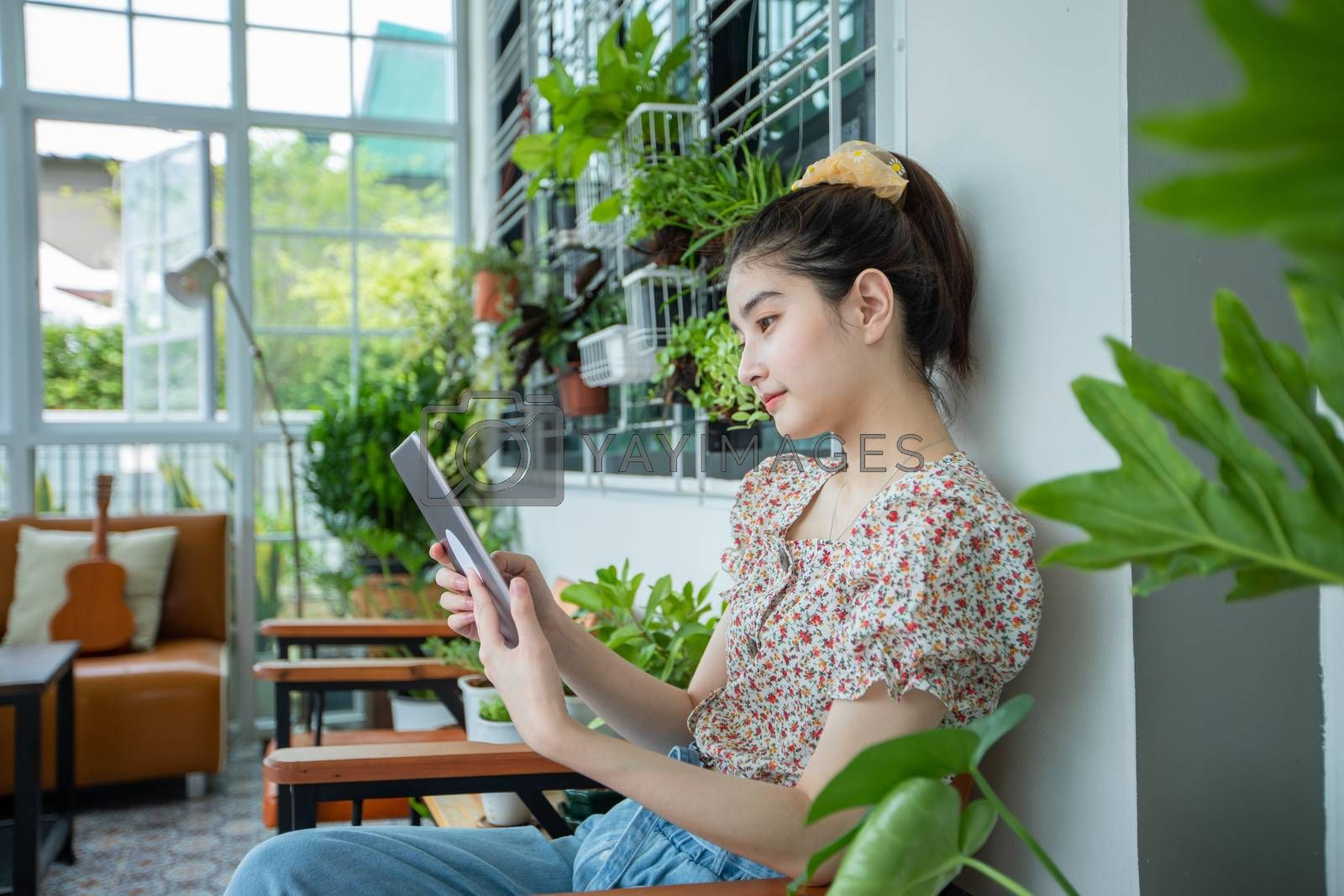 Asian woman is using digital tablet for read news and shopping online in the garden at home in relaxing time