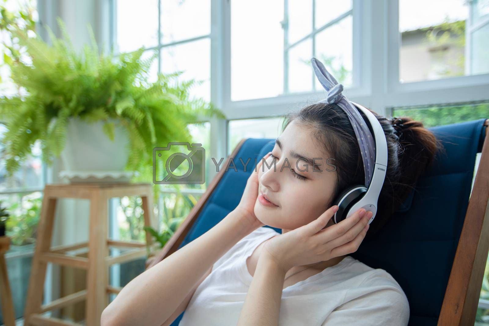 Beautiful Asian women wear headphones and use a notebook computer to work and listen to music in the garden at home on a relaxing day.