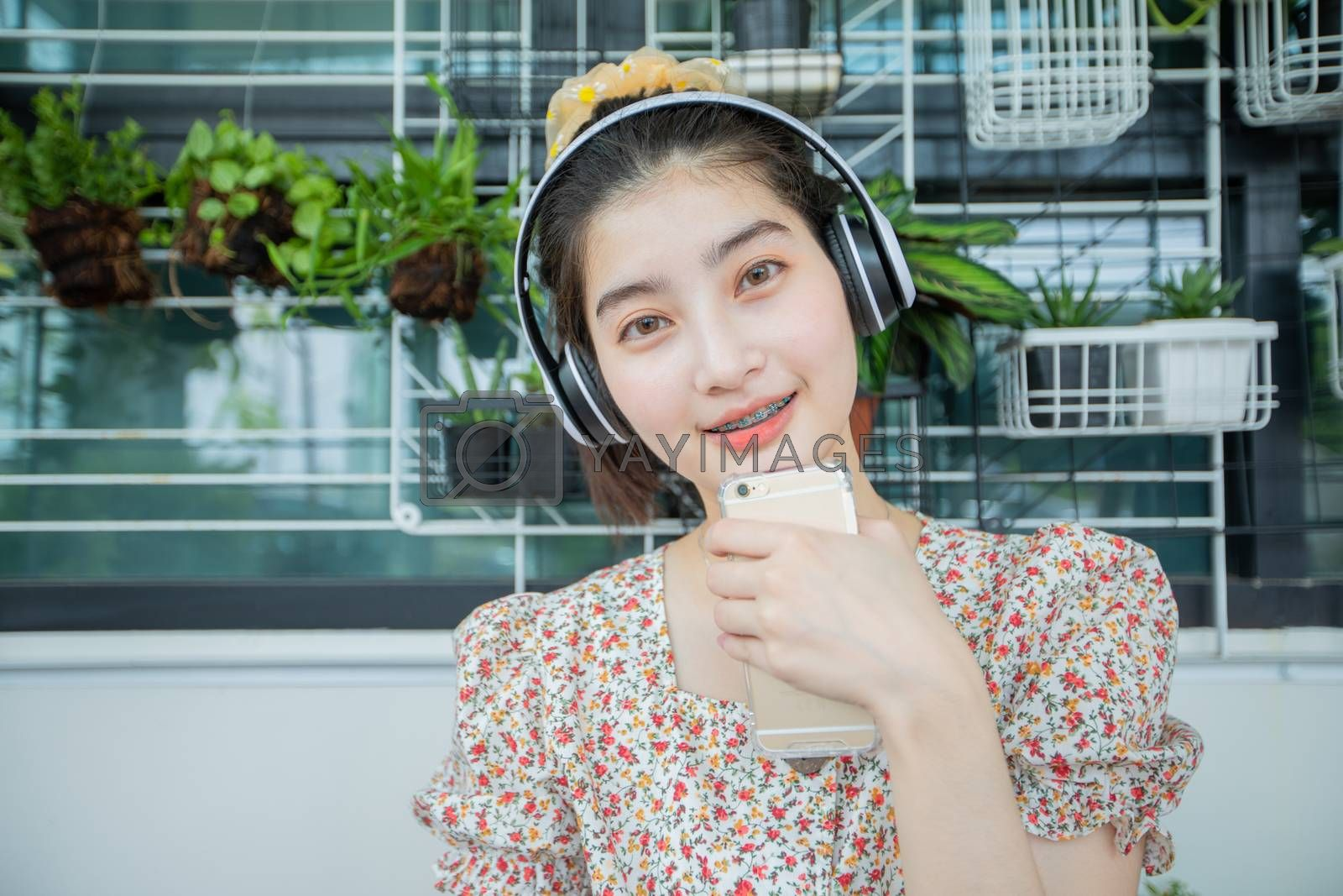 Asian women wearing headphones and using mobile phone and digital tablet for Listening to music and singing on a relaxing day at home