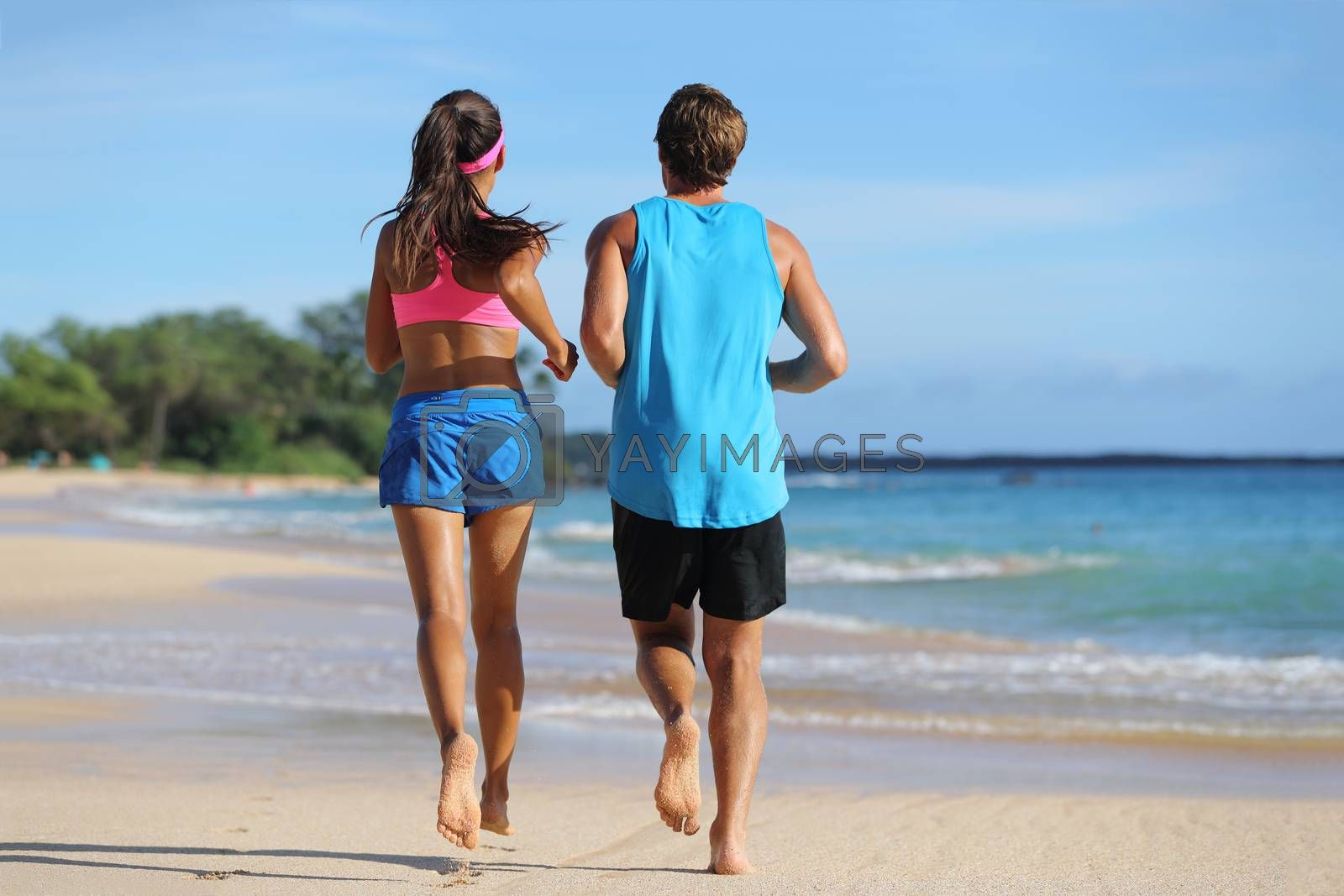 Two fitness athletes running together on beach. People from behind jogging away barefoot on sand on tropical travel destination. Healthy fit young adults with muscular slim legs training cardio.