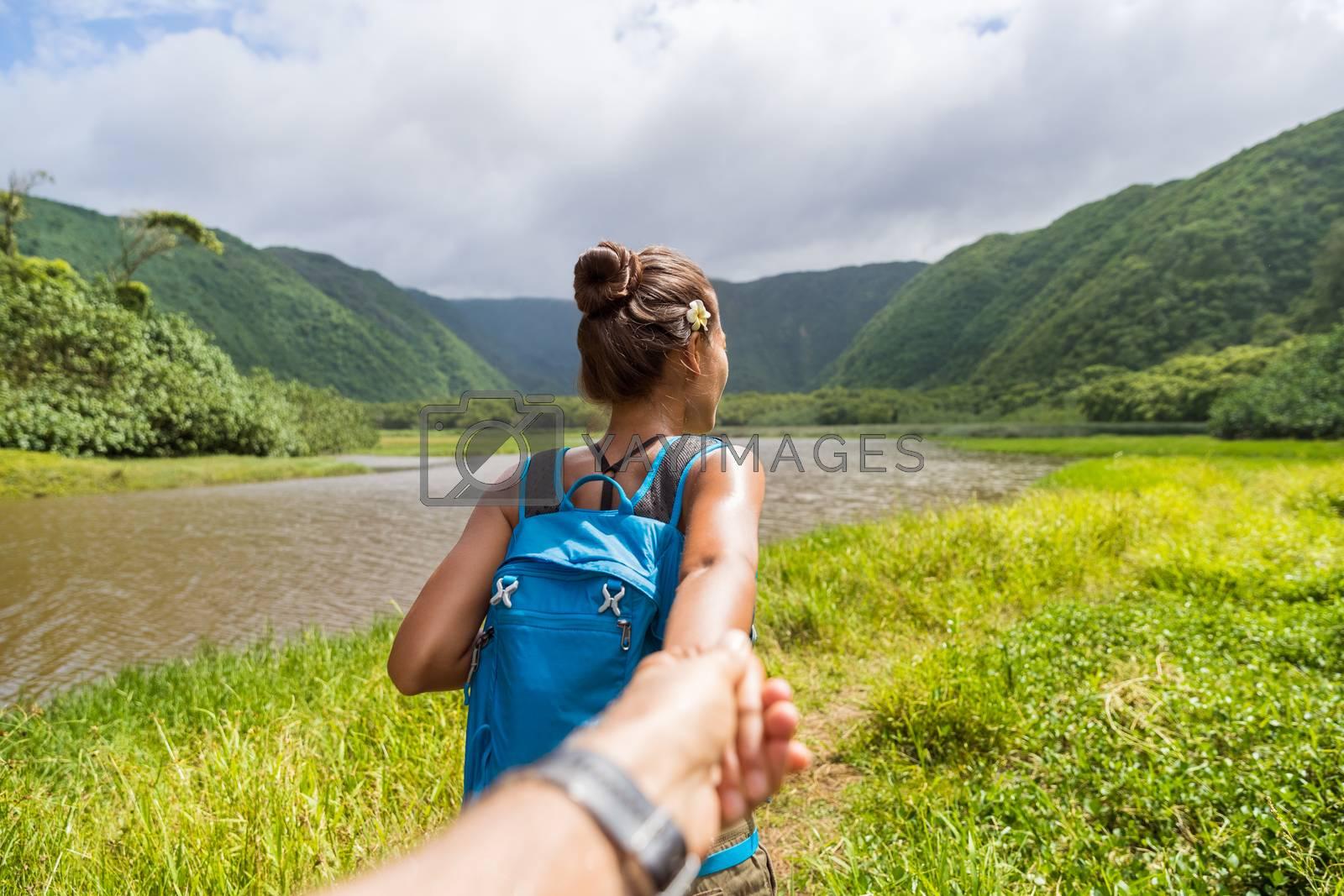 Hawaii travel nature hiker follow me woman hiking in Pololu valley holding hand of boyfriend following leading girlfriend walking. Big island destination, woman tourist in Hawaii, USA.