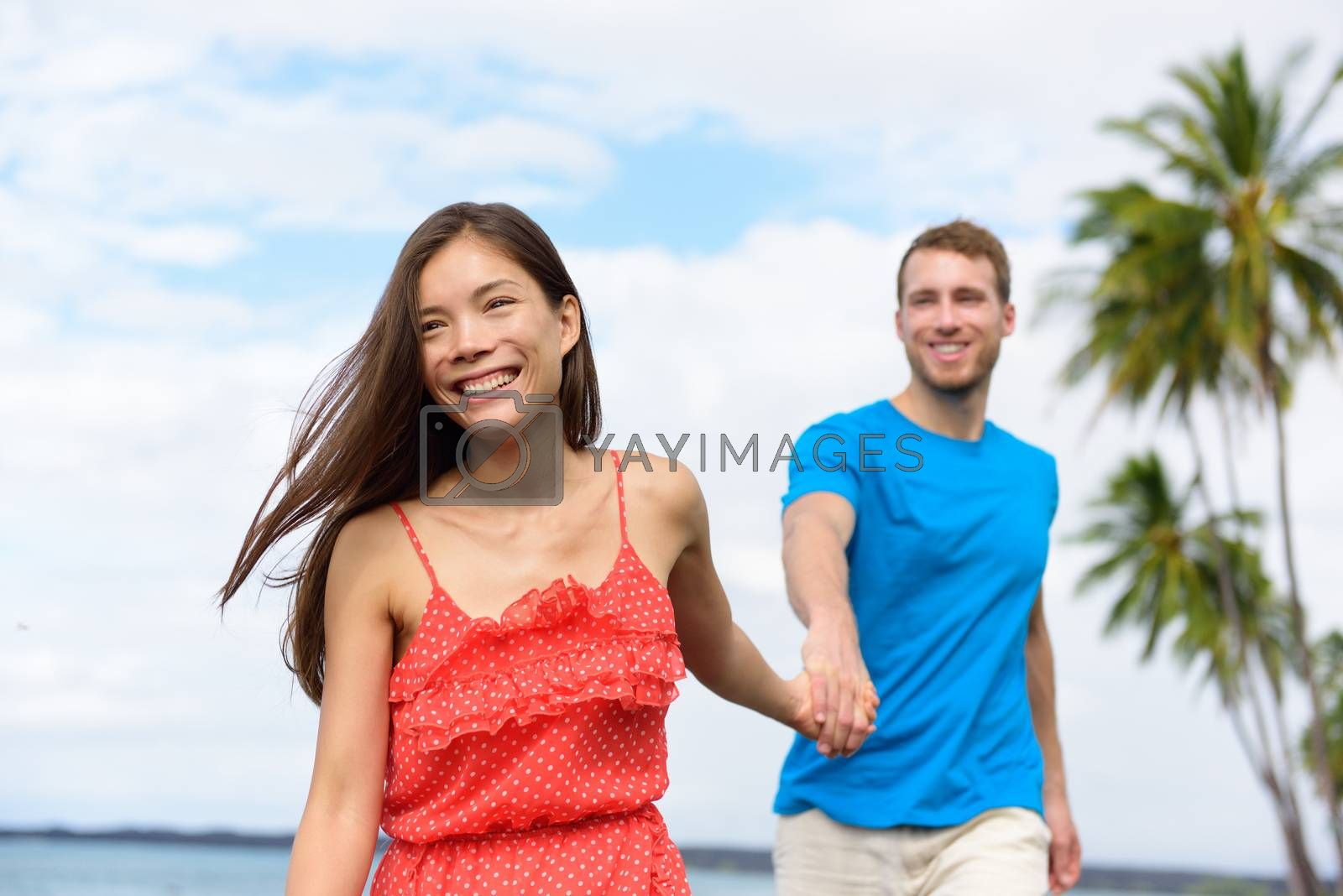 Happy summer vacation couple walking holding hands on beach travel destination. Asian woman caucasian man multiracial people together having fun.