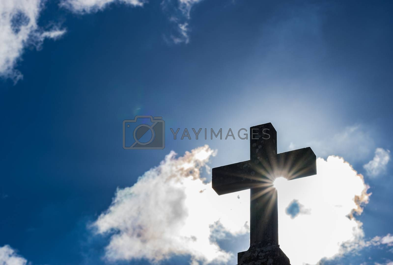 Cross against blue cloudy sky with sunlight, religion christianity concepts background