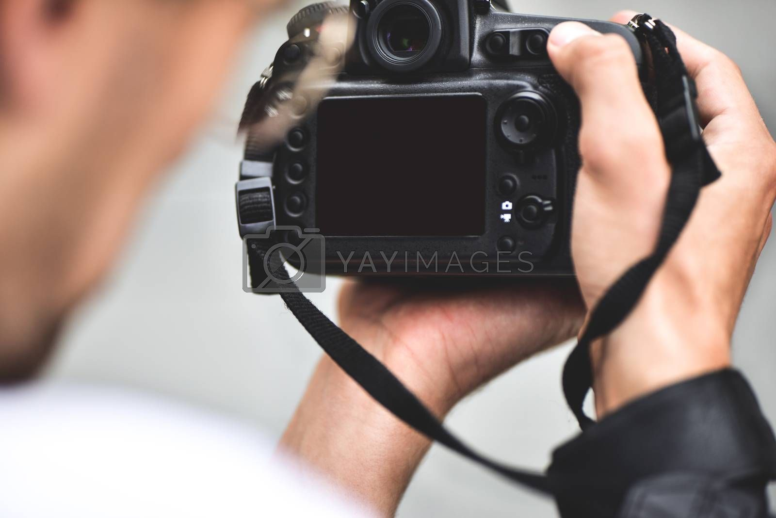 Close up male hands hold professional camera and make a photo. by Nickstock