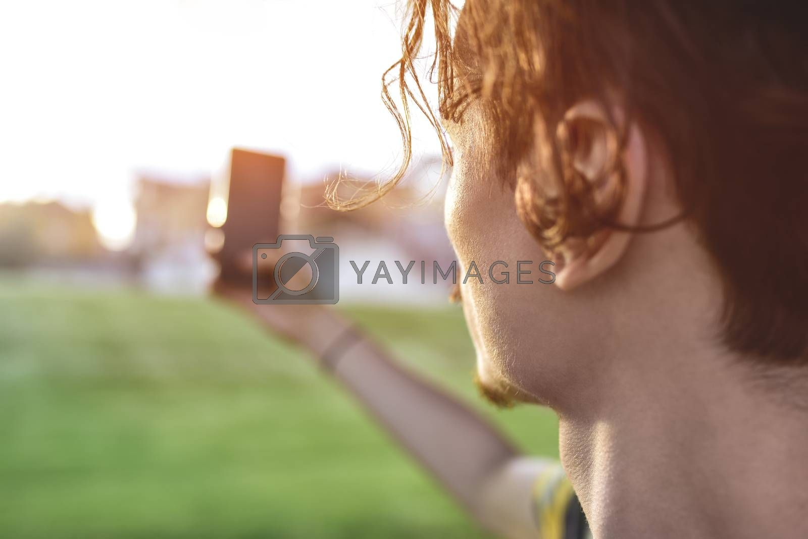 close-up guy takes pictures of nature, beautiful views on his smartphone. free copyspace by Nickstock
