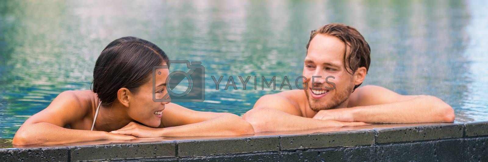 Wellness spa pool couple relaxing in hydrotherapy luxury travel resort on tropical holidays together enjoying the swim in water. Banner panorama. Hotel swimming pool.