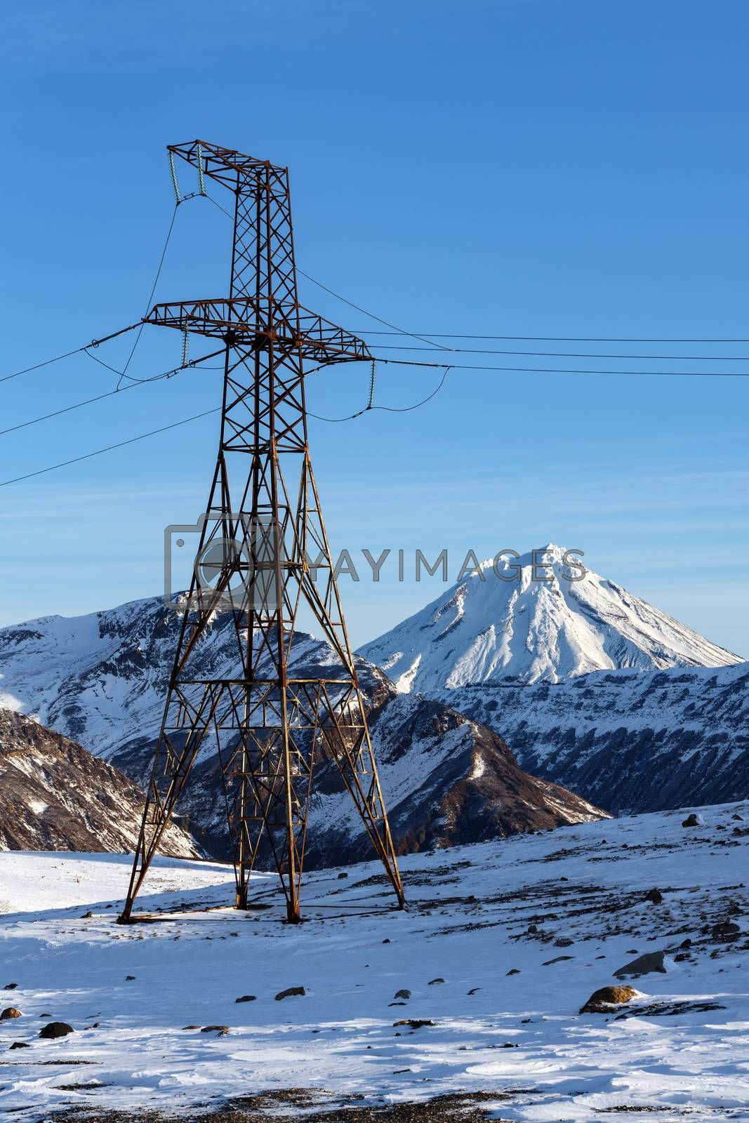 High voltage power line at winter sunny day. View on high voltage metal tower in mountain on background of snow-capped cone of Vilyuchinsky Volcano. Kamchatka Peninsula, Russian Far East, Eurasia.