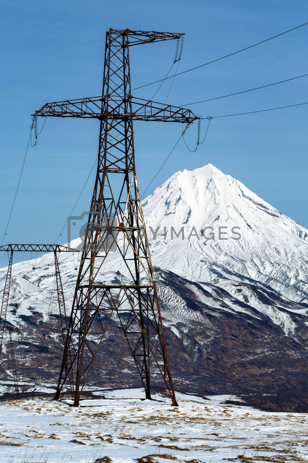 High voltage power line on clear sunny day. View on high voltage metal towers in mountain on background of snowcapped cone of Vilyuchinsky Volcano. Kamchatka Peninsula, Russian Far East, Eurasia.