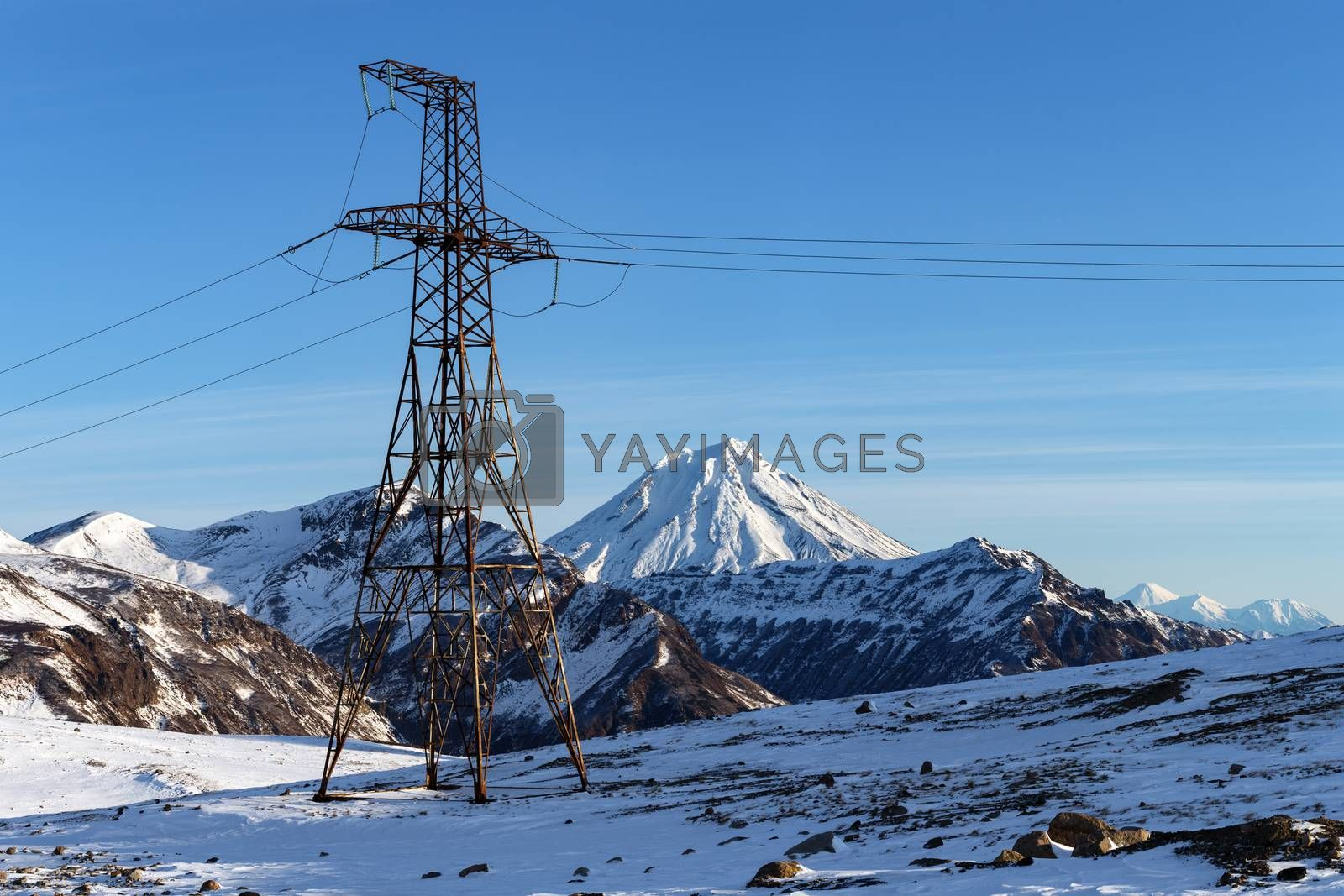 High voltage metal tower in highlands on sunny winter weather. View on high voltage power line on background of snow-capped cone of Vilyuchinsky Volcano. Eurasia, Russian Far East, Kamchatka Peninsula