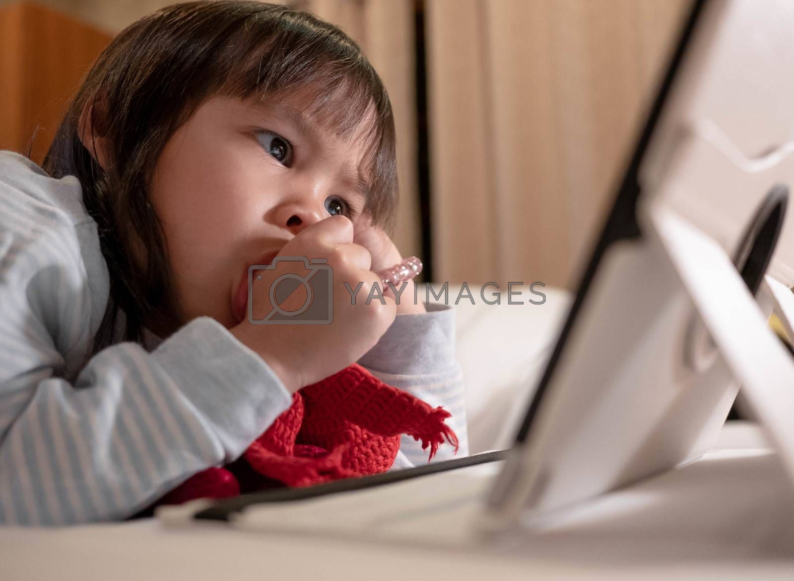 Cute little girl lying on bed with sucking her thumb and looking on a digital tablet in bedroom.